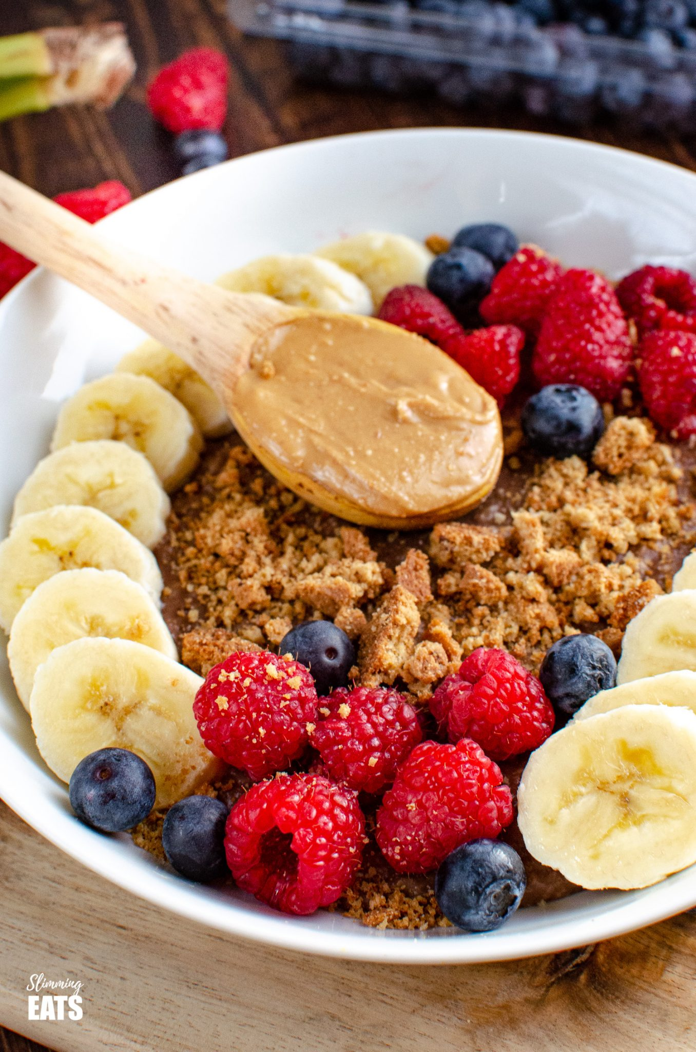 Chocolate Peanut Butter Oatmeal in white bowl with wooden spoon of peanut butter, slices of banana, raspberries, blueberries and a mini crumbled cookie
