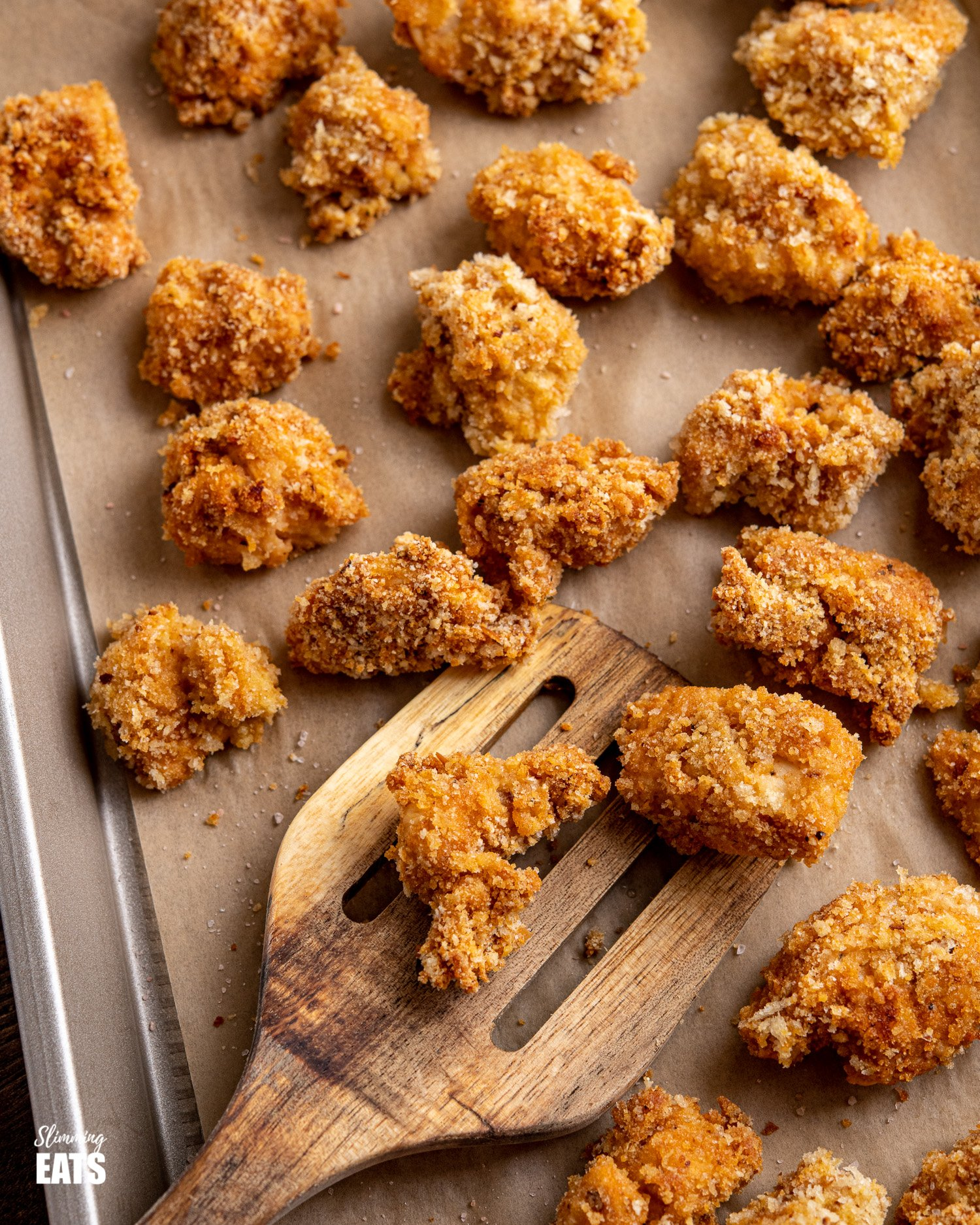 close up of oven baked popcorn chicken bites on a parchment lined baking tray with wooden spatula