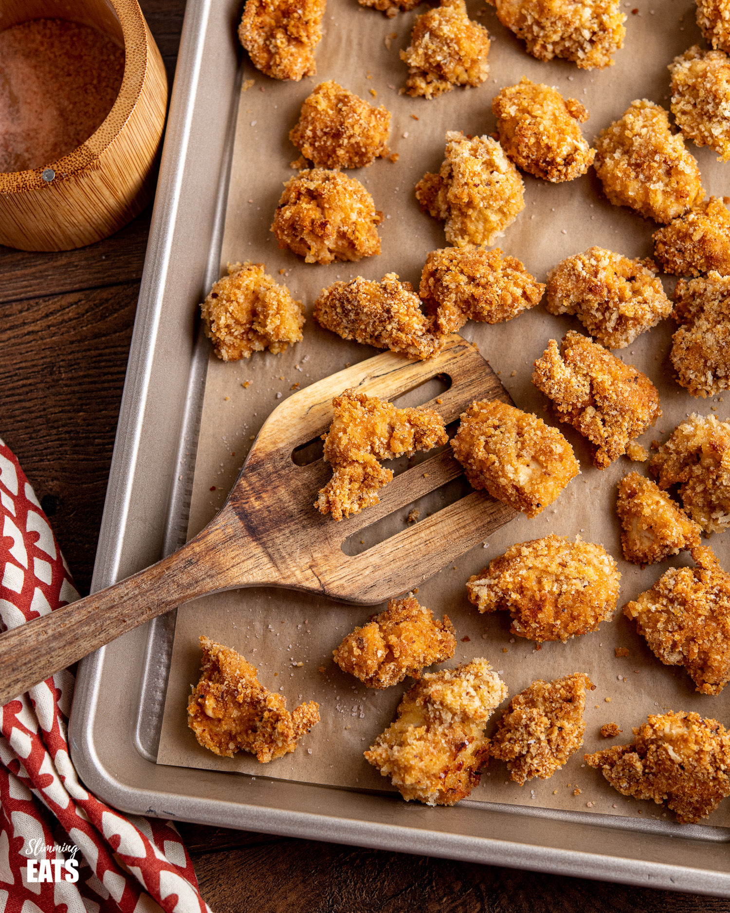 oven baked popcorn chicken bites on a parchment lined baking tray with wooden spatula