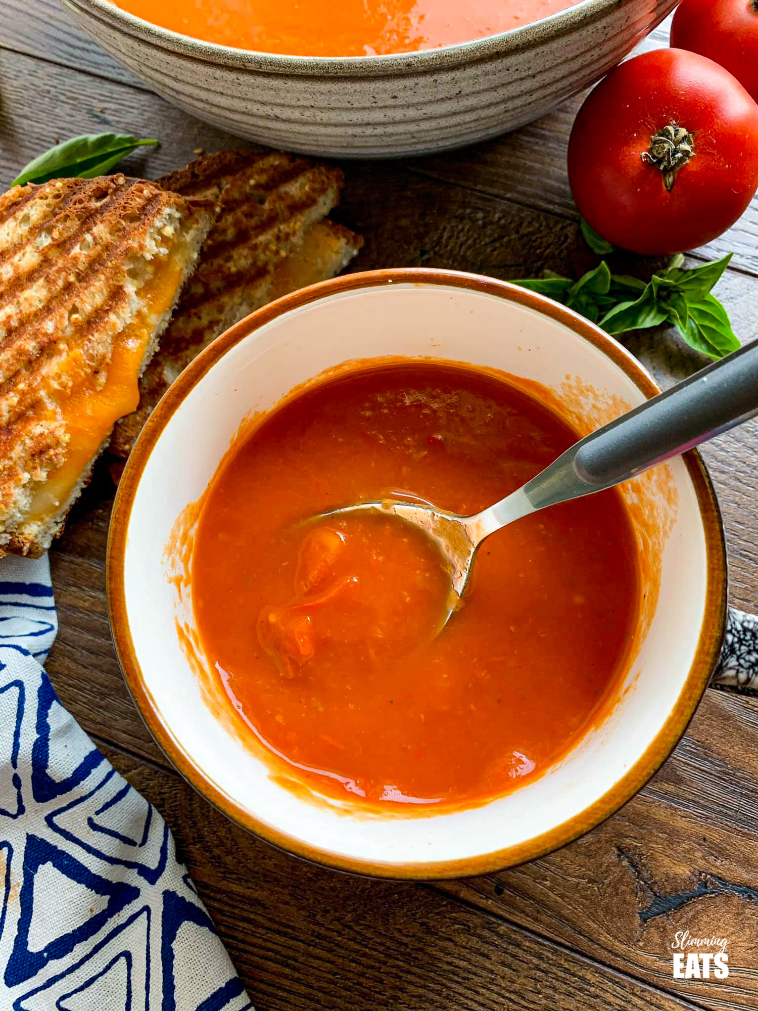 Roasted Red Pepper and Tomato Soup in cup with grilled cheese to the left and tomatoes on the right