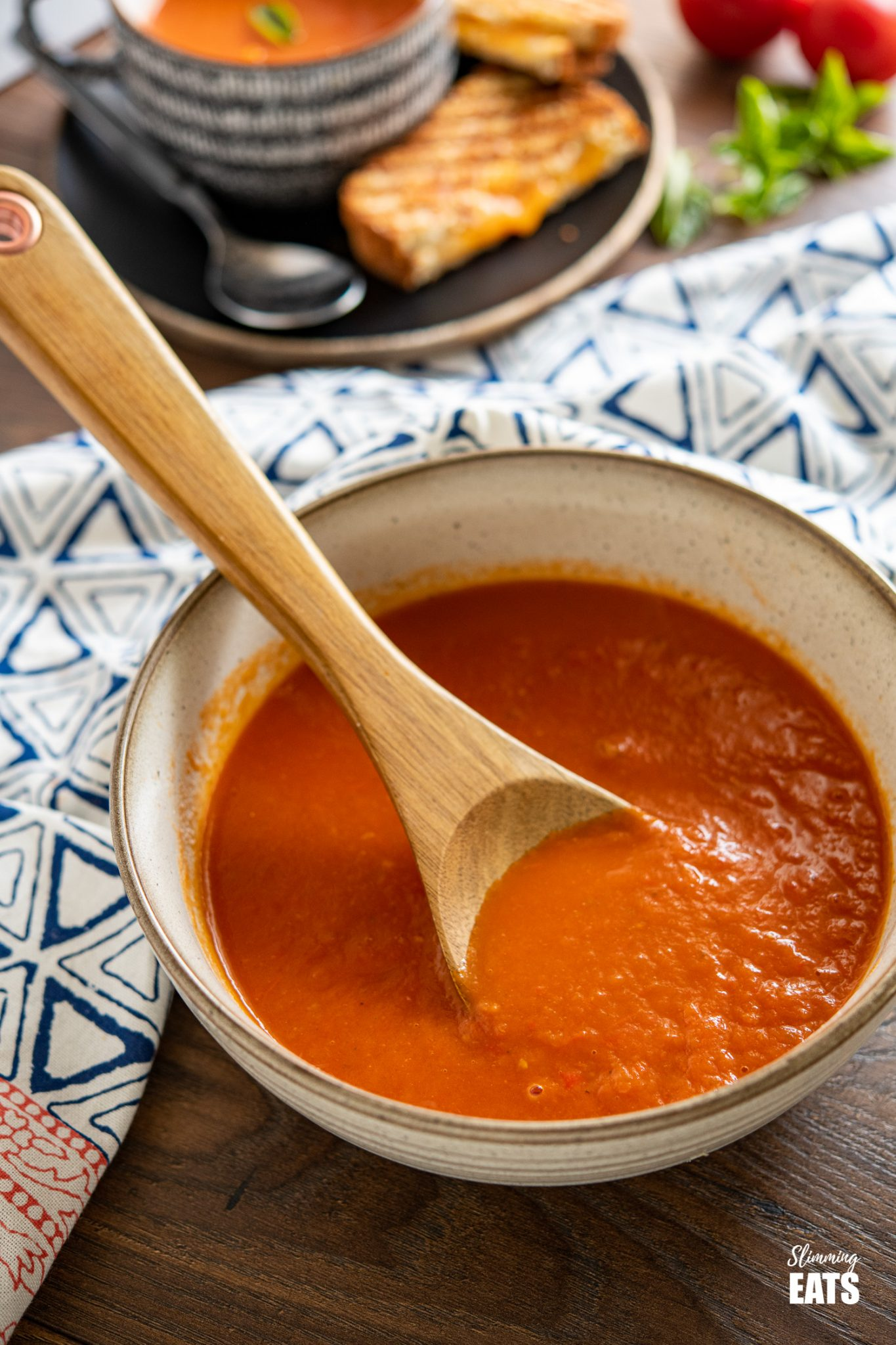 large speckled brown bowl of roasted pepper and tomato soup with wooden spoon