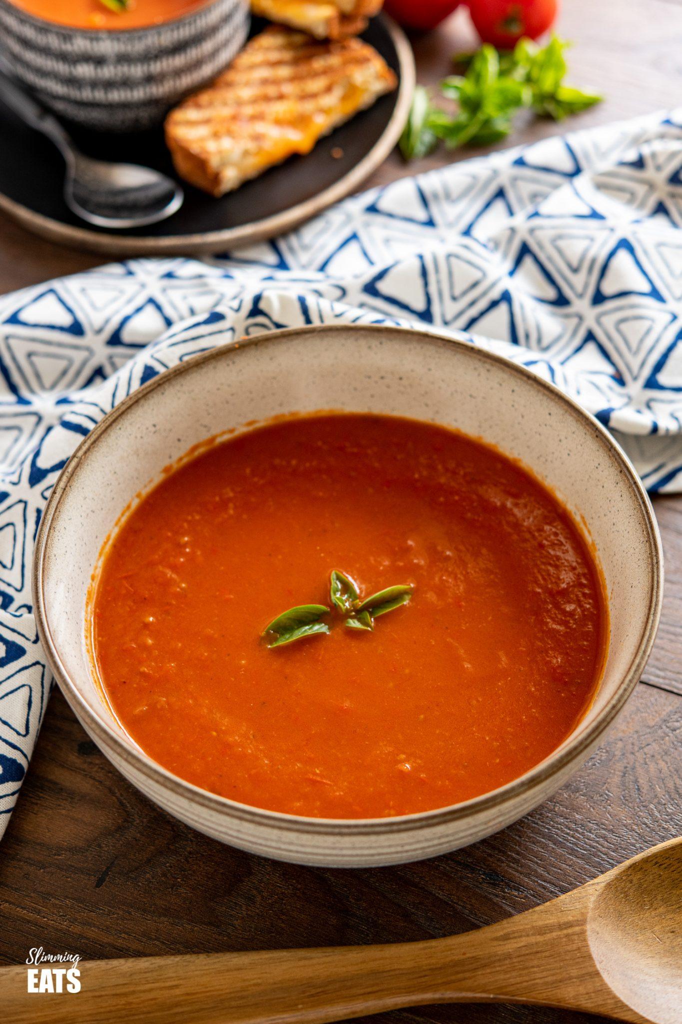 Grand bol brun tacheté de poivron rouge rôti et soupe de tomates avec une cuillère en bois à l'avant