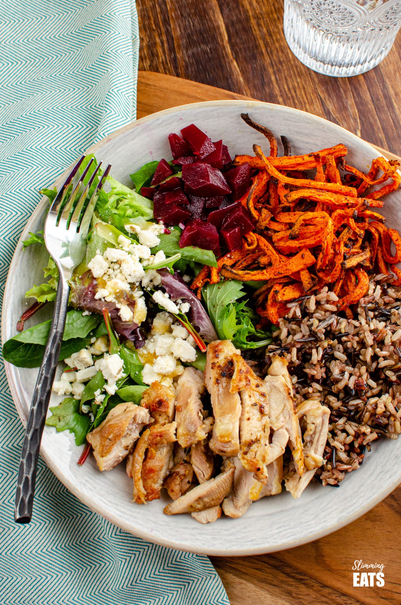 Chicken Wild Rice Bowl - tender seasoned chicken thighs with a delicious nutty wild rice blend, roasted carrot strands, salad with beets and feta in a bowl with fork