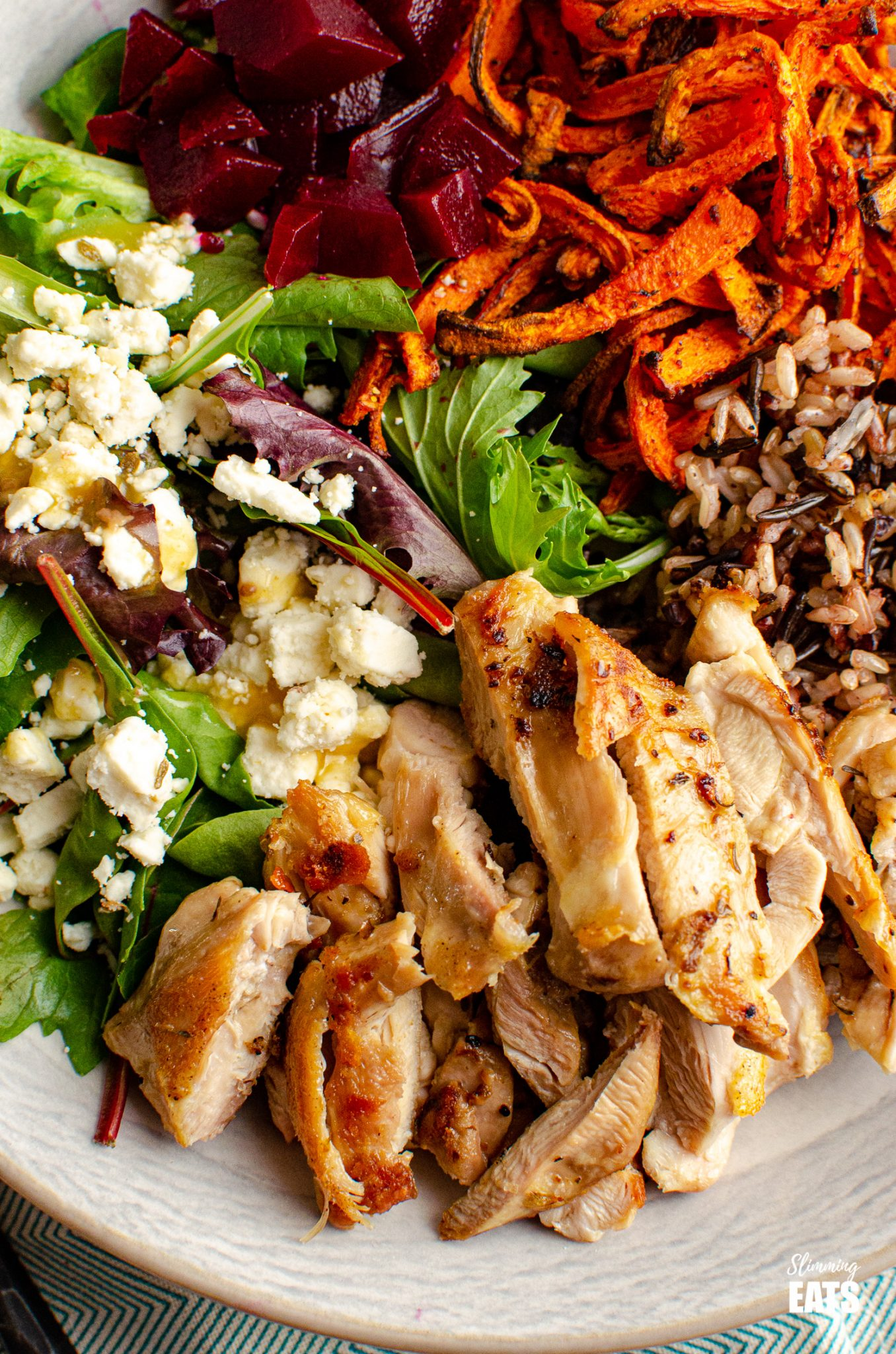 close up of Tender seasoned chicken thighs with a delicious nutty wild rice blend, roasted carrot strands, salad with beets and feta in a bowl with fork