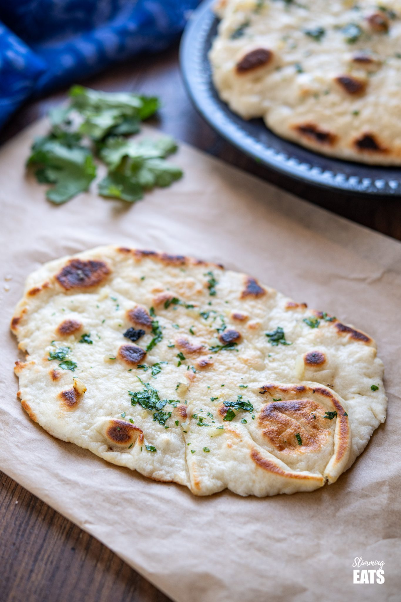 Garlic Greek Yoghurt Naan Bread on a sheet or parchment paper with scattered cilantro
