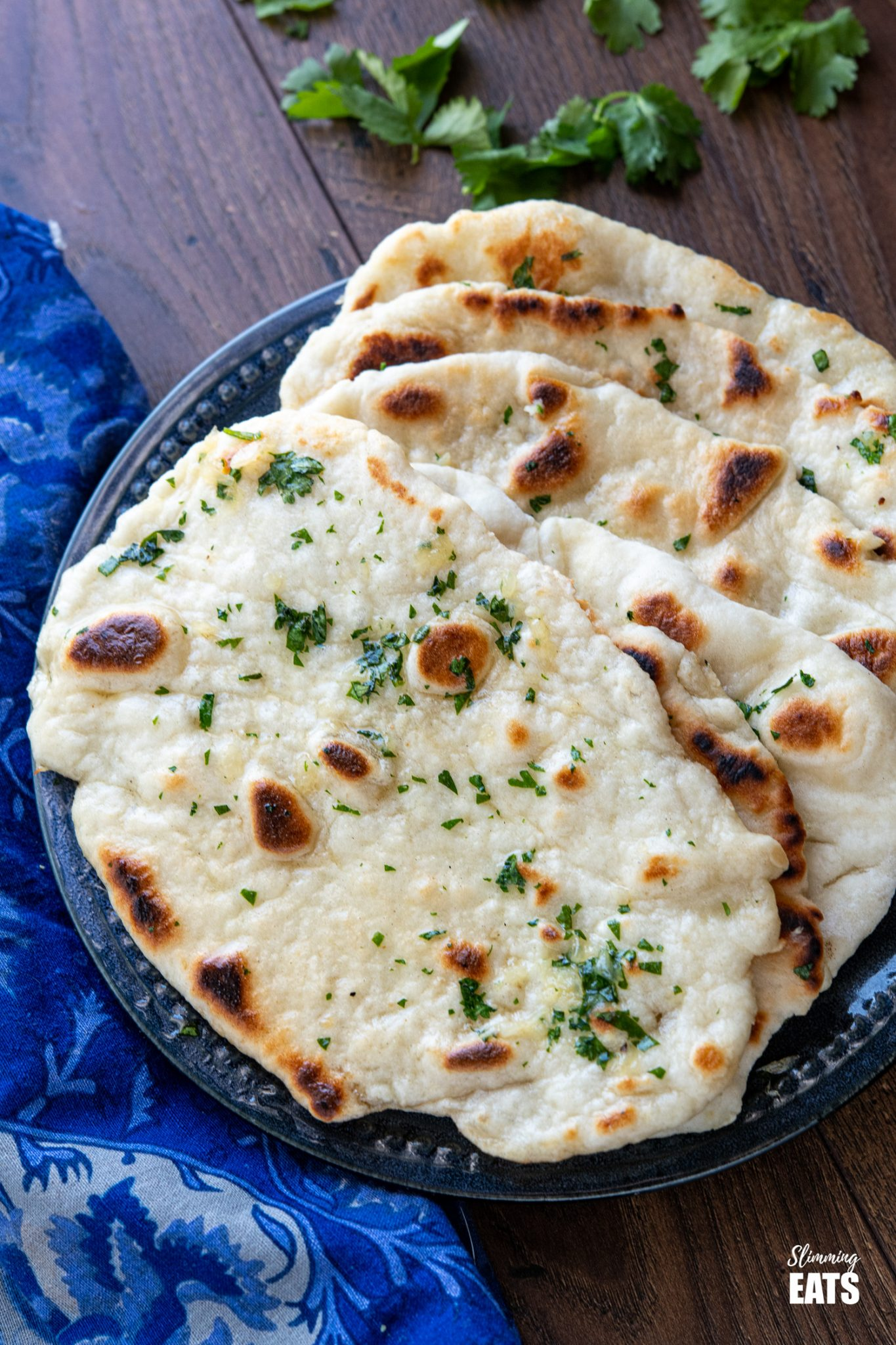 close up of Garlic Greek Yoghurt Naan Bread on dark blue plate with scattered cilantro