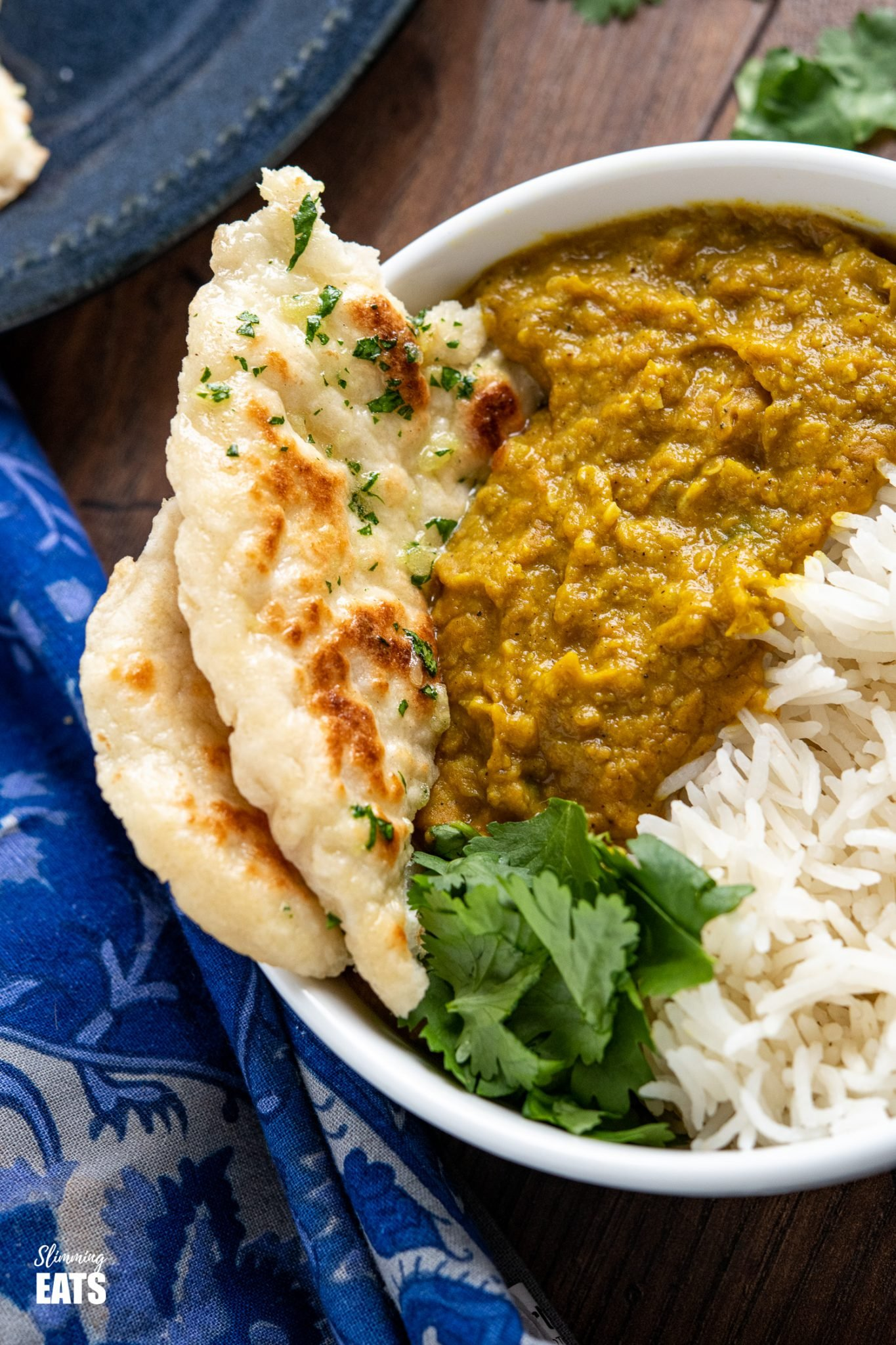 close up of Garlic Greek Yoghurt Naan Bread in white bowl with dhal and rice