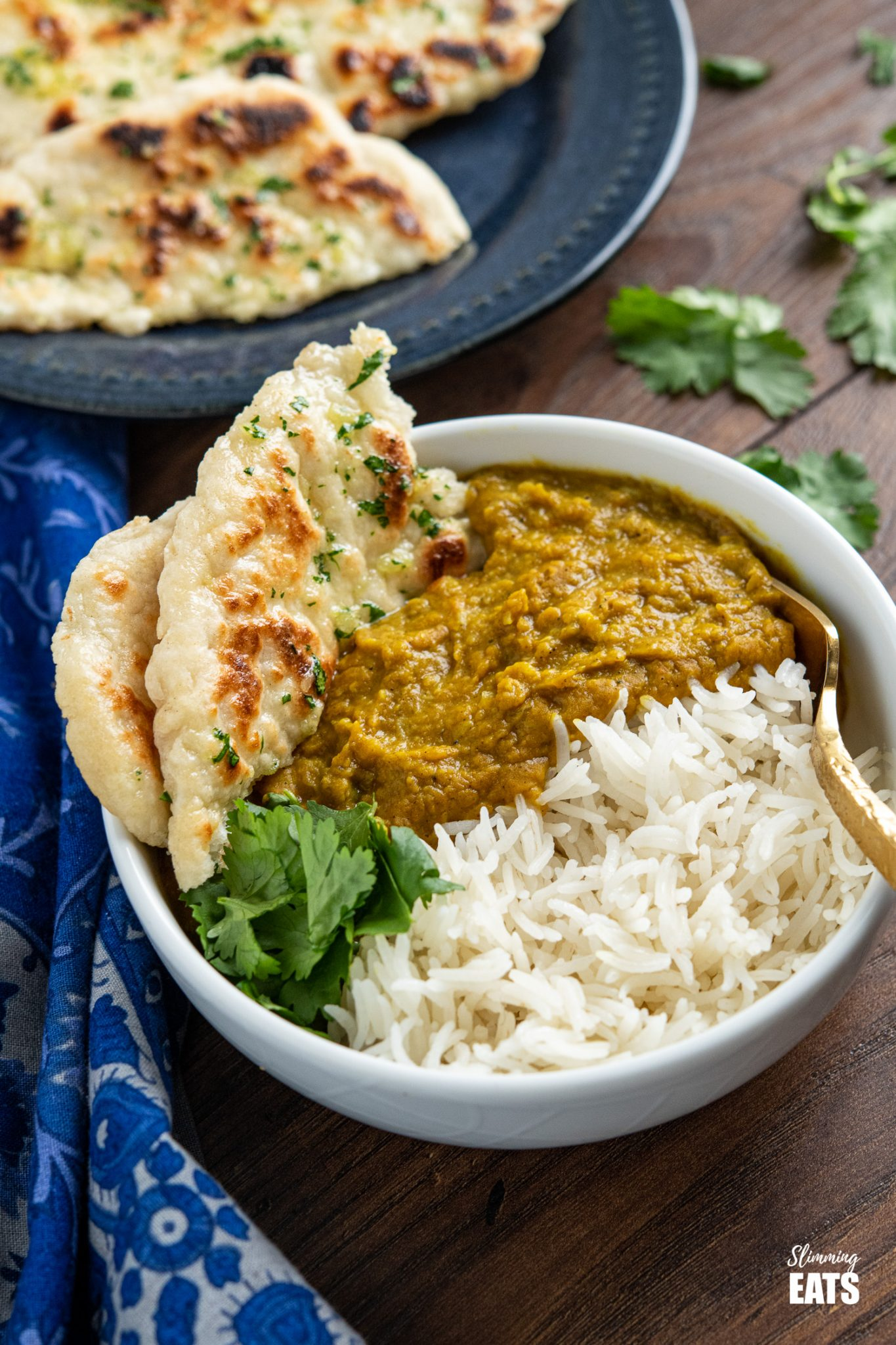 Garlic Greek Yoghurt Naan Bread in white bowl with dhal and rice