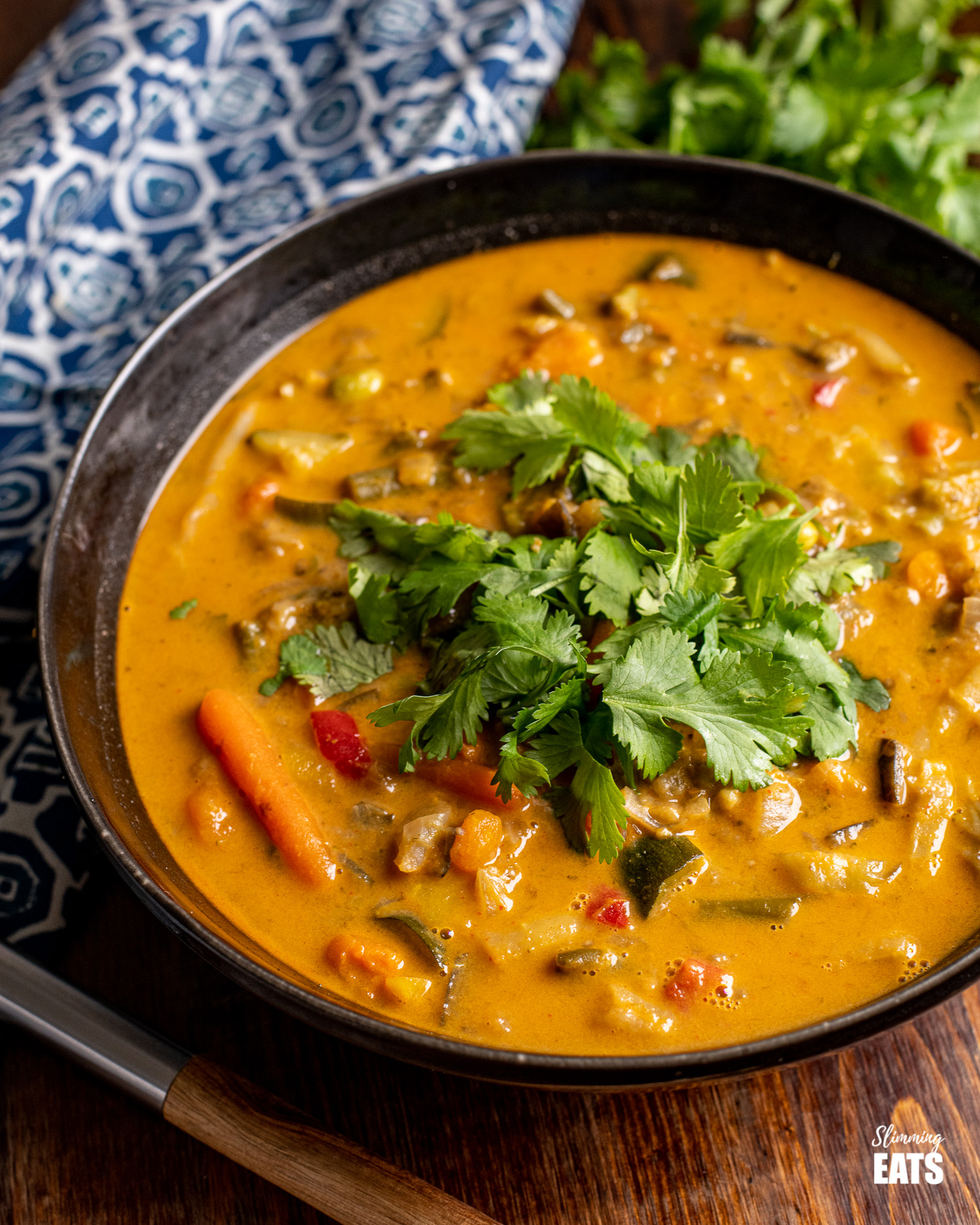 Thai Vegetable Soup in a black bowl topped with coriander