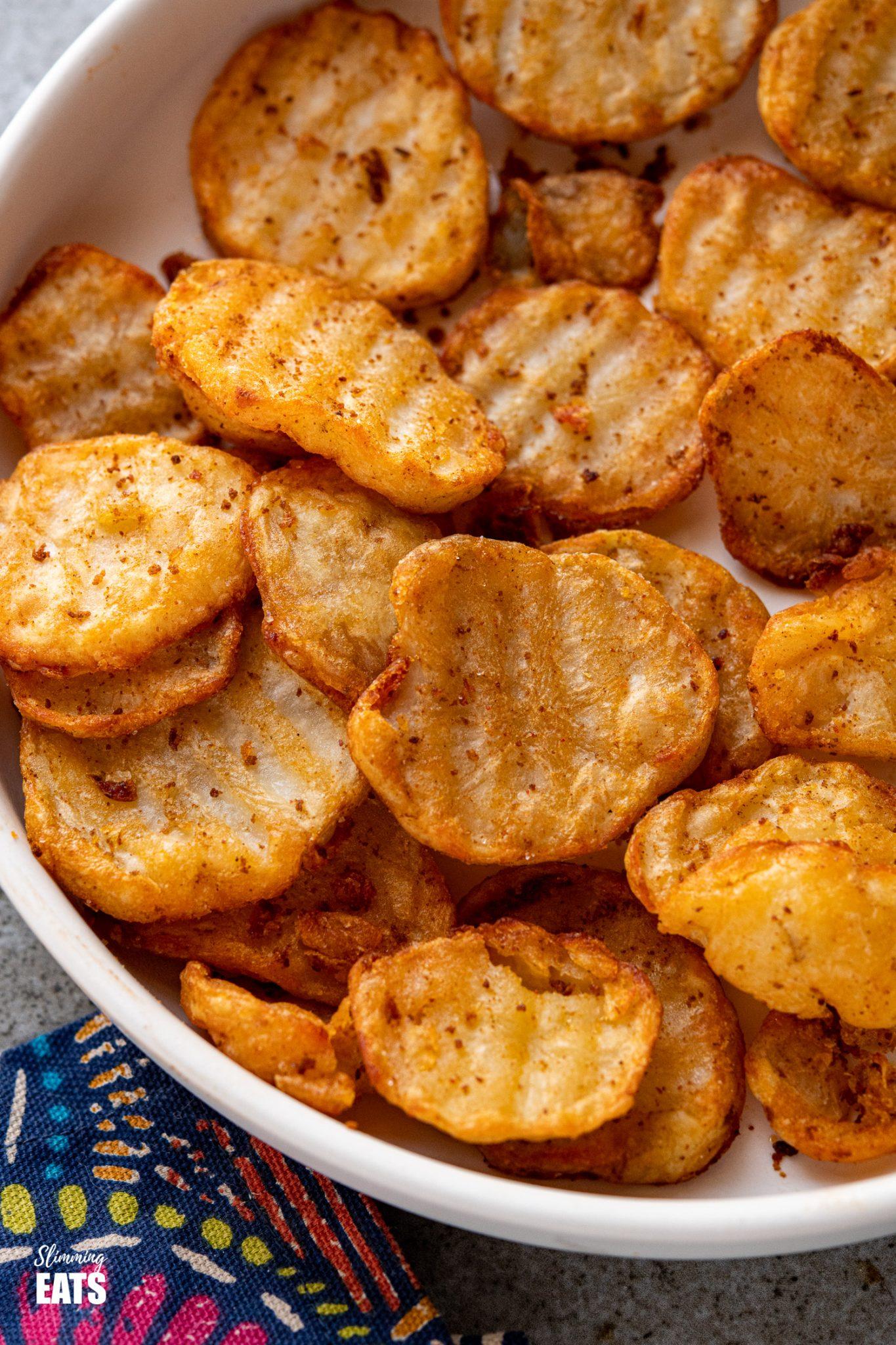 close up of crispy potato slices in white bowl