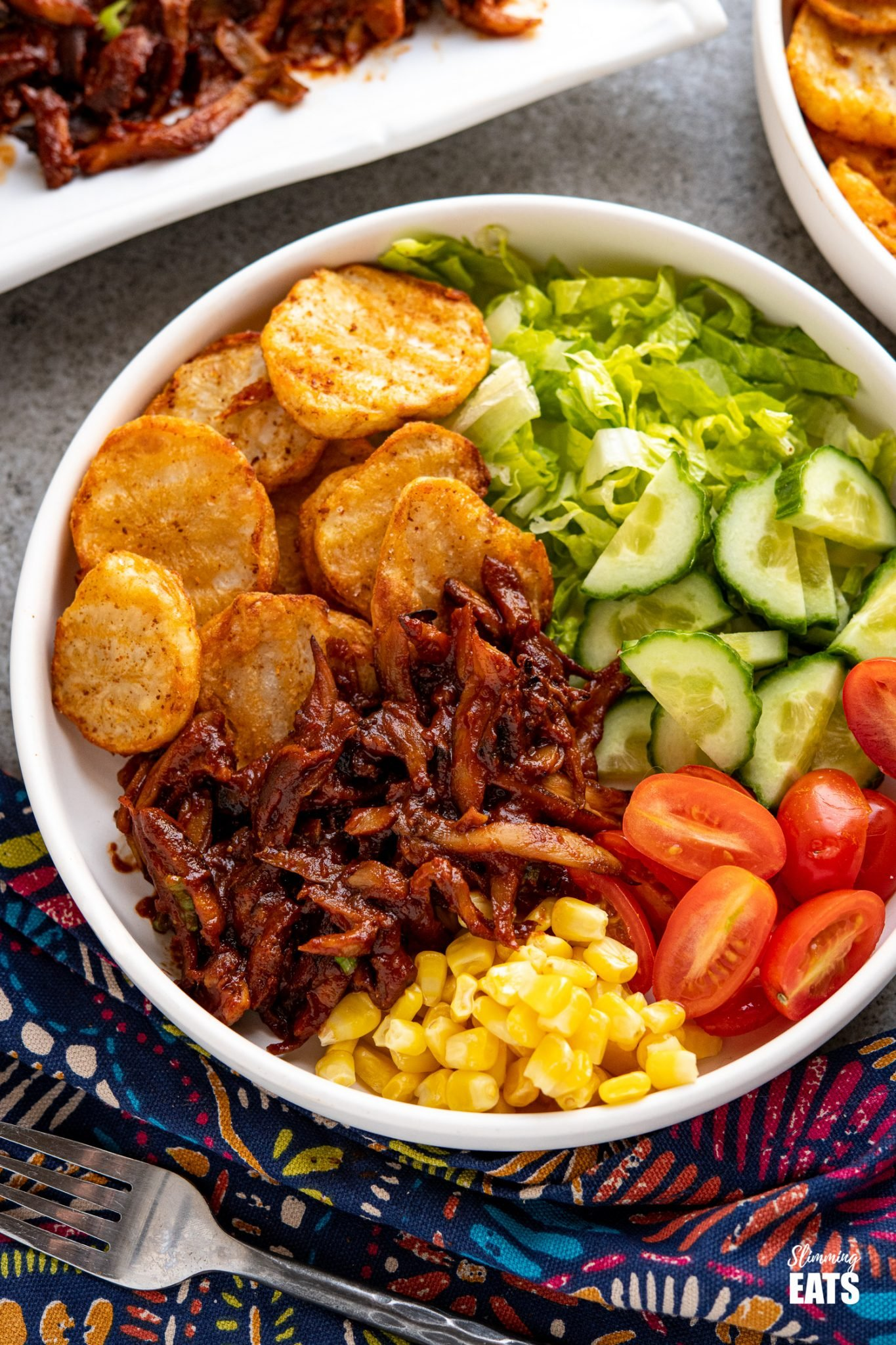 Pulled Mushrooms with BBQ Sauce in white bowl with crispy potato slices, corn and salad.
