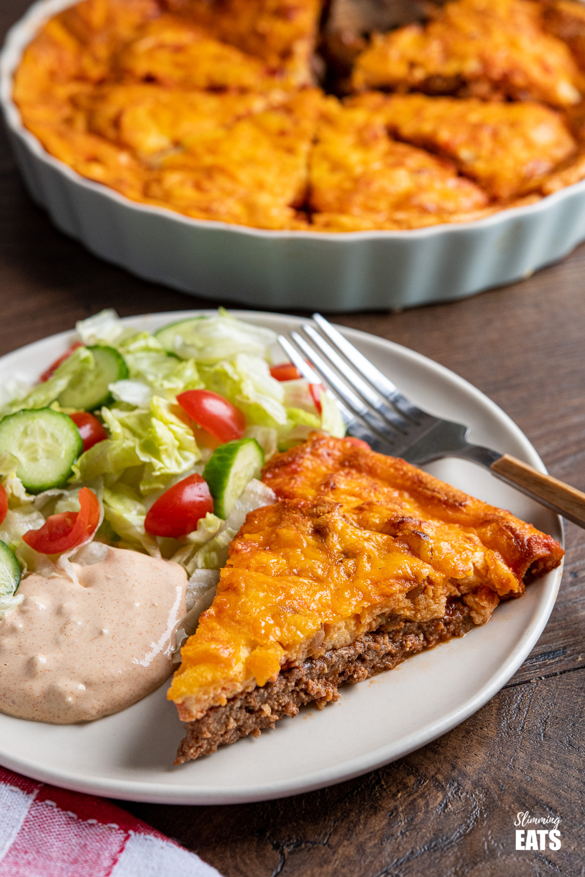 slice of cheeseburger quiche on a plate with burger sauce and salad