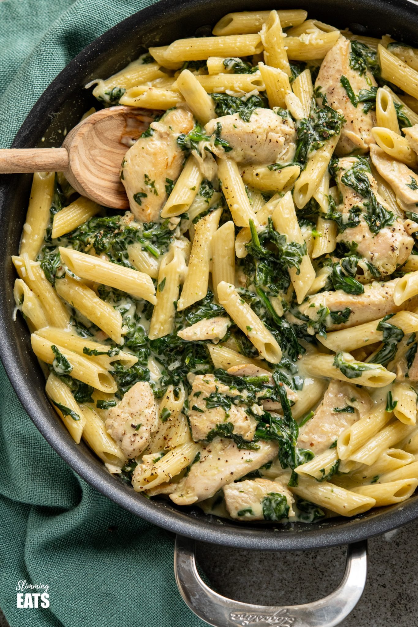 close up of creamy garlic chicken with spinach penne pasta in black frying pan with wooden spoon