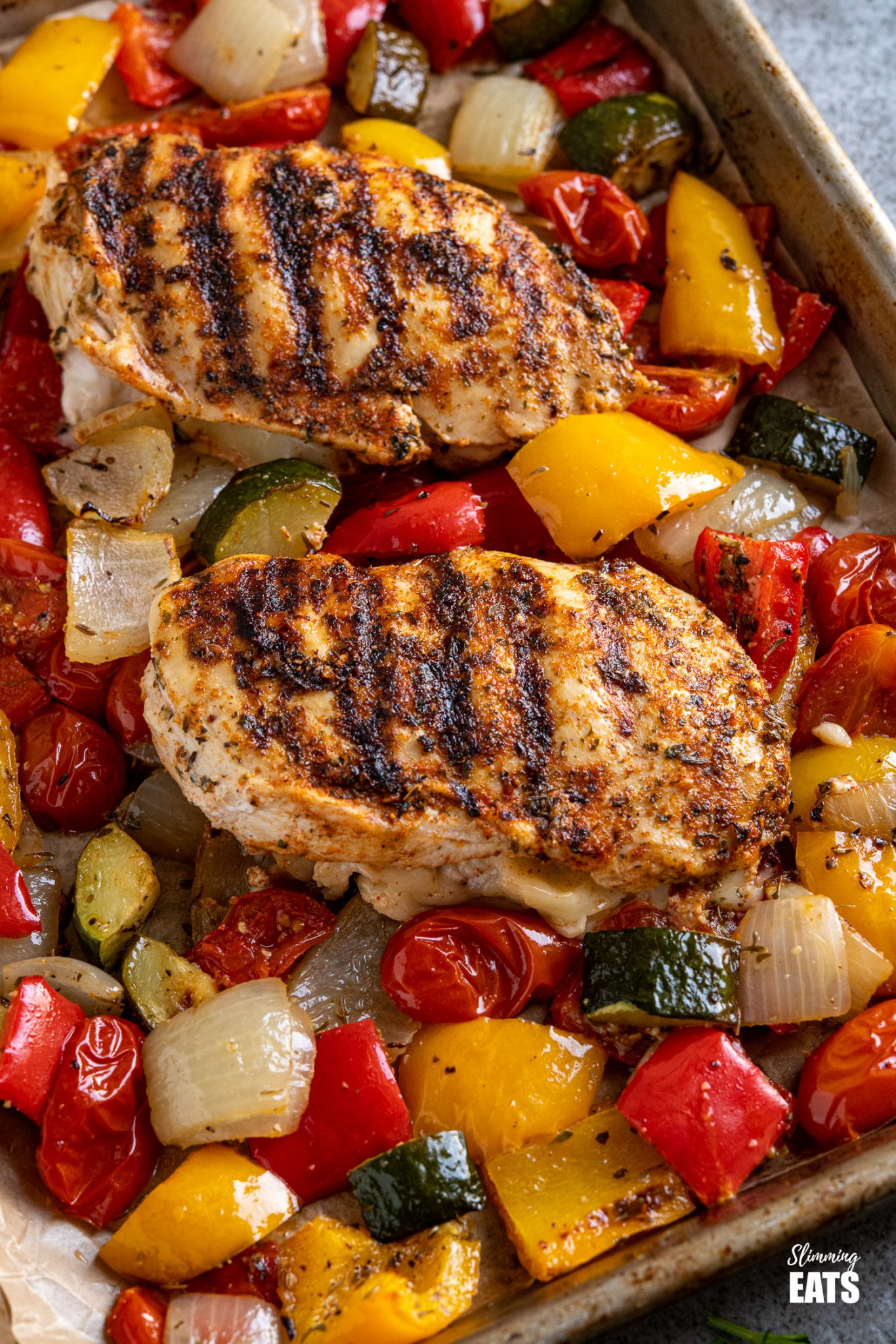 close up of two grilled chicken stuffed with mozzarella and roasted vegetables on a baking tray line with parchment paper