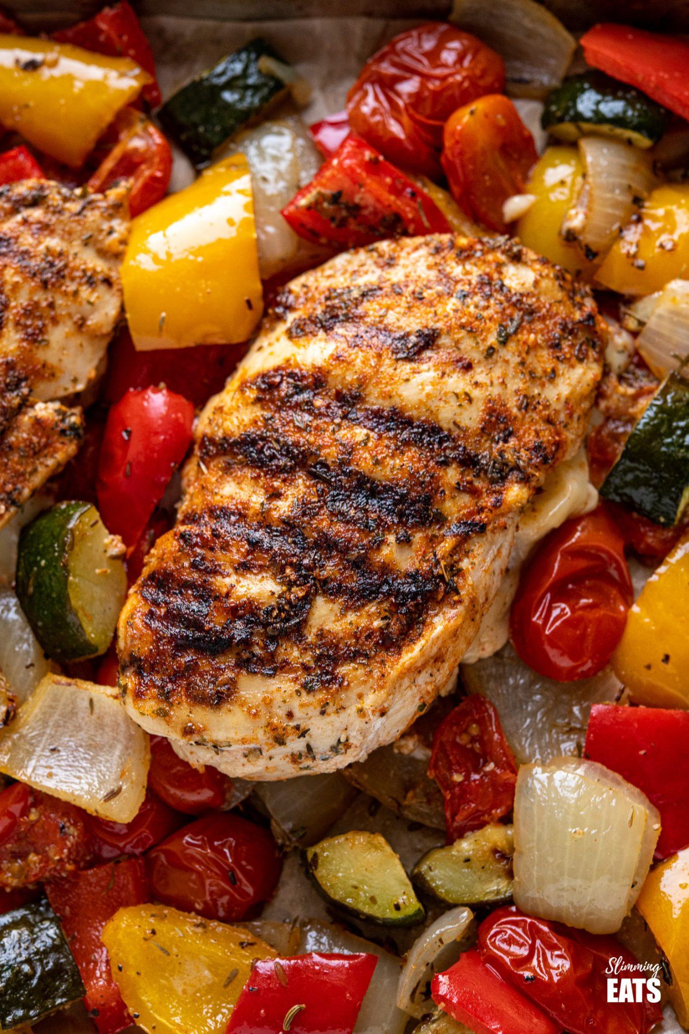 close up of grilled chicken stuffed with mozzarella and roasted vegetables on a baking tray line with parchment paper with wooden spatula