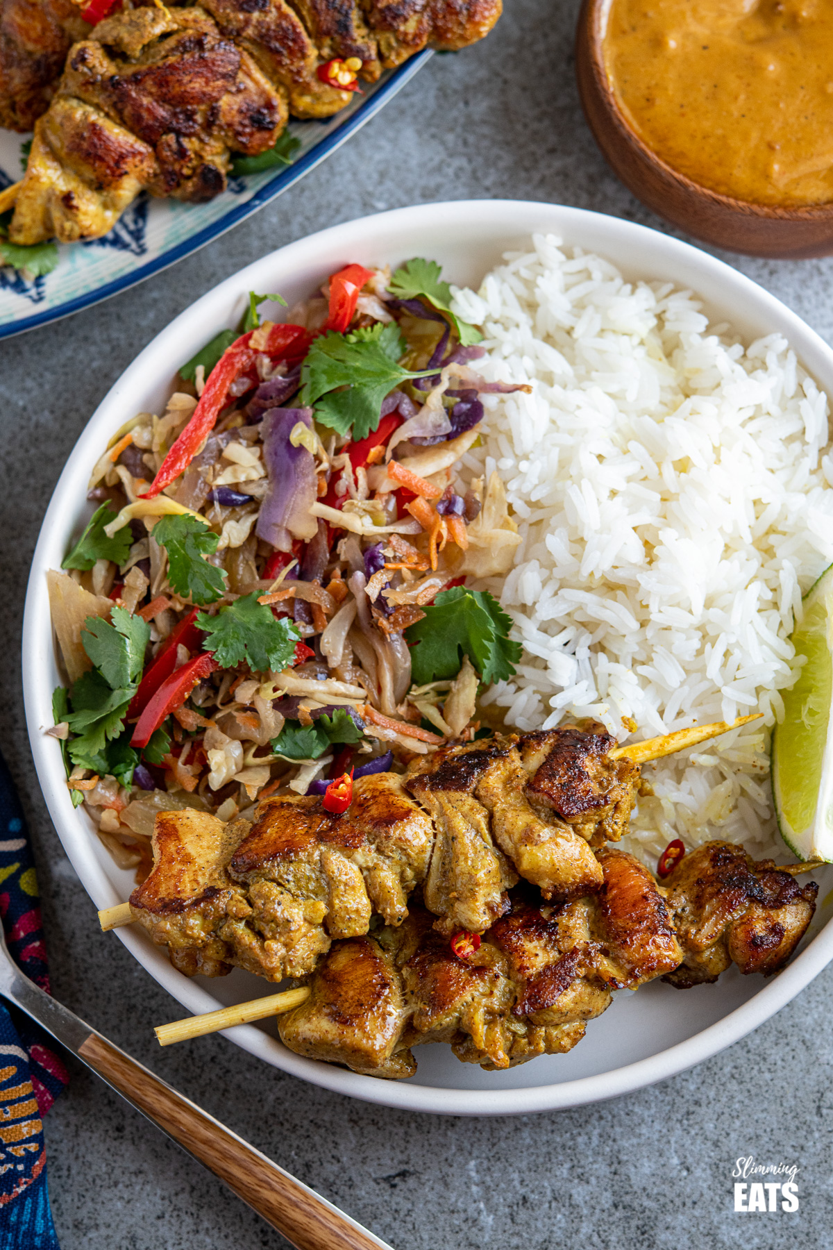 Chicken Satay skewers, rice, veggies and lime wedge on a white plate