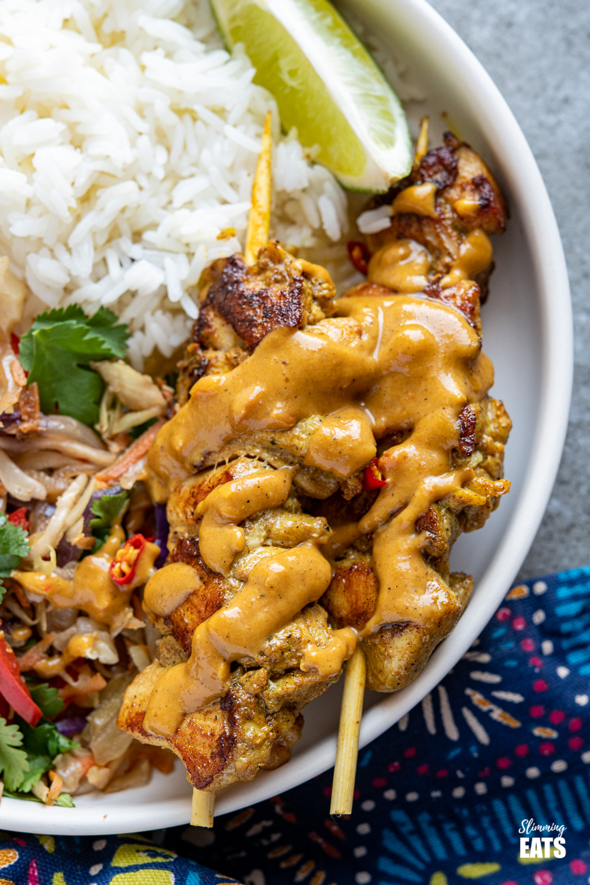 close up of Chicken Satay with Peanut Sauce , rice, veggies and lime wedge on a white plate