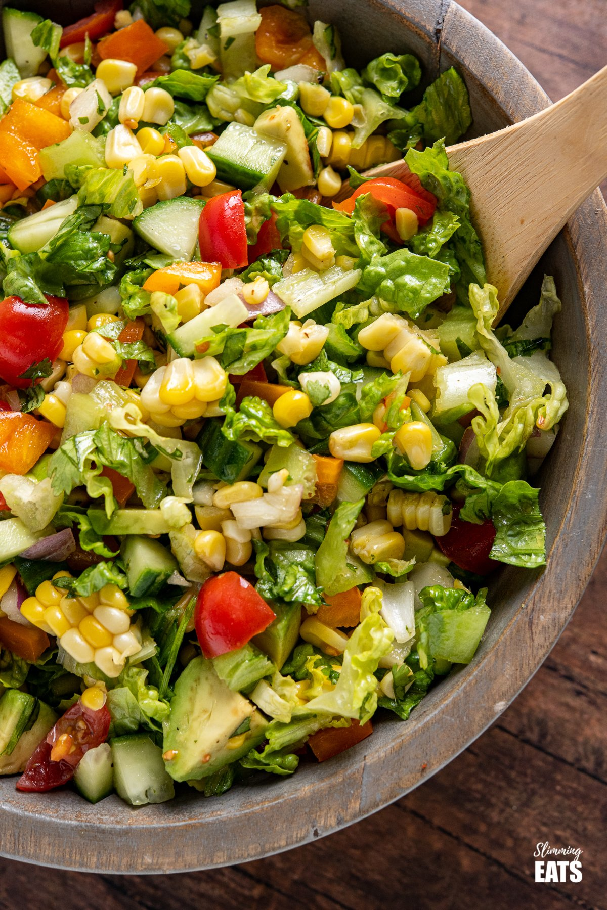 close up of chopped salad in wooden bowl with wooden spoon