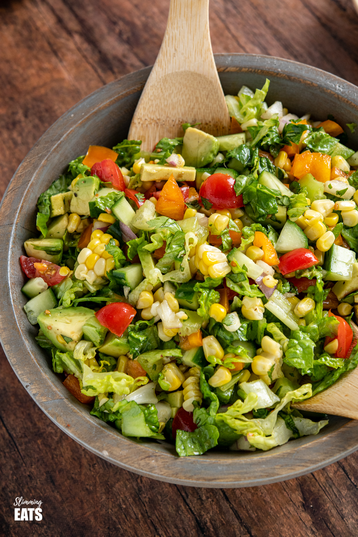 chopped salad in wooden bowl with wooden spoons