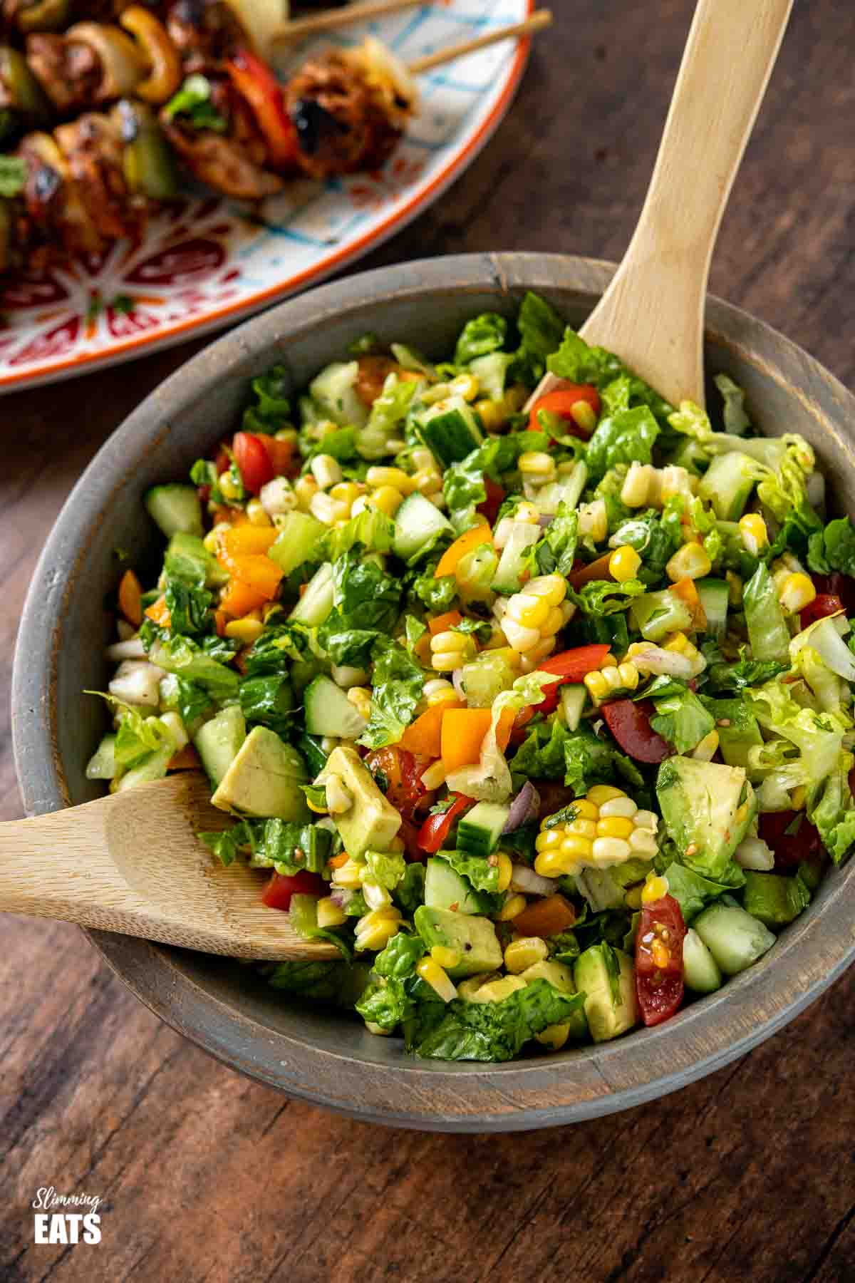 chopped salad in wooden bowl with wooden spoons with plate of chicken skewers behind