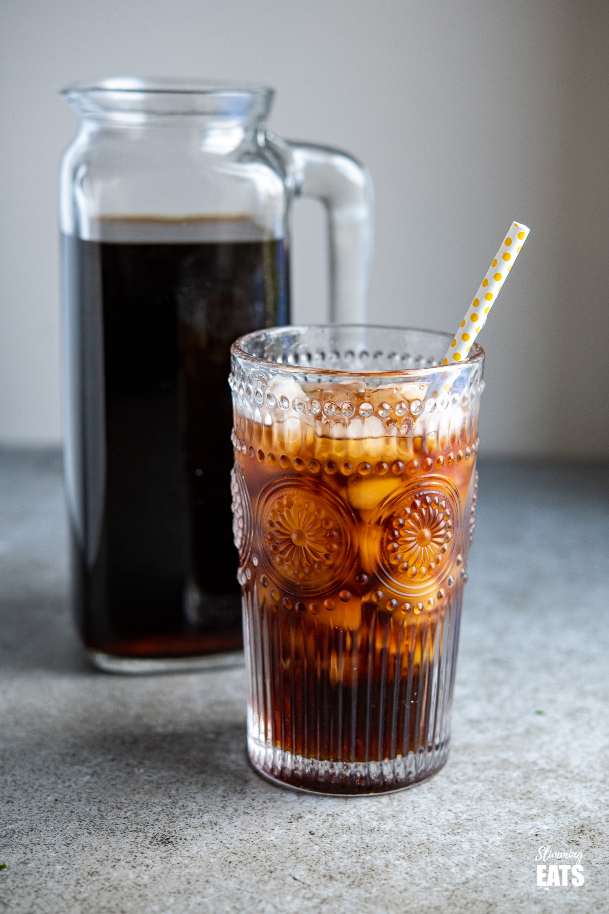 cold brew coffee with ice in a glass with yellow spotted white straw, jug of cold brew in background