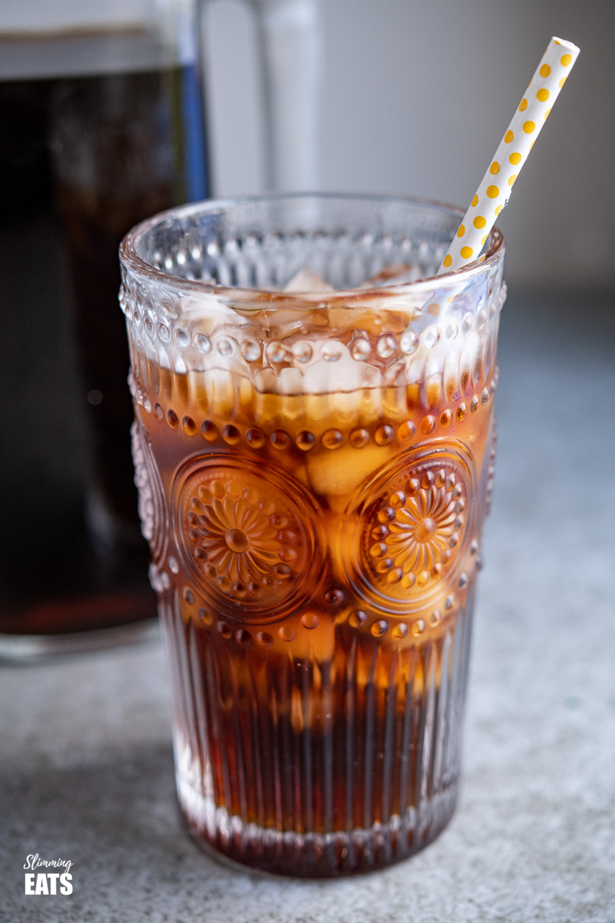 close up of cold brew coffee with ice in a glass with yellow spotted white straw, jug of cold brew in background