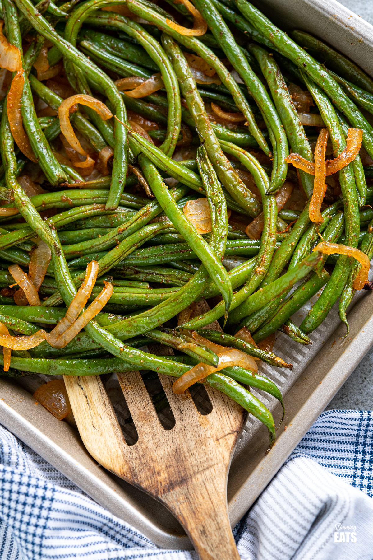 close up of Roasted Green Beans on a baking tray with wooden spatula