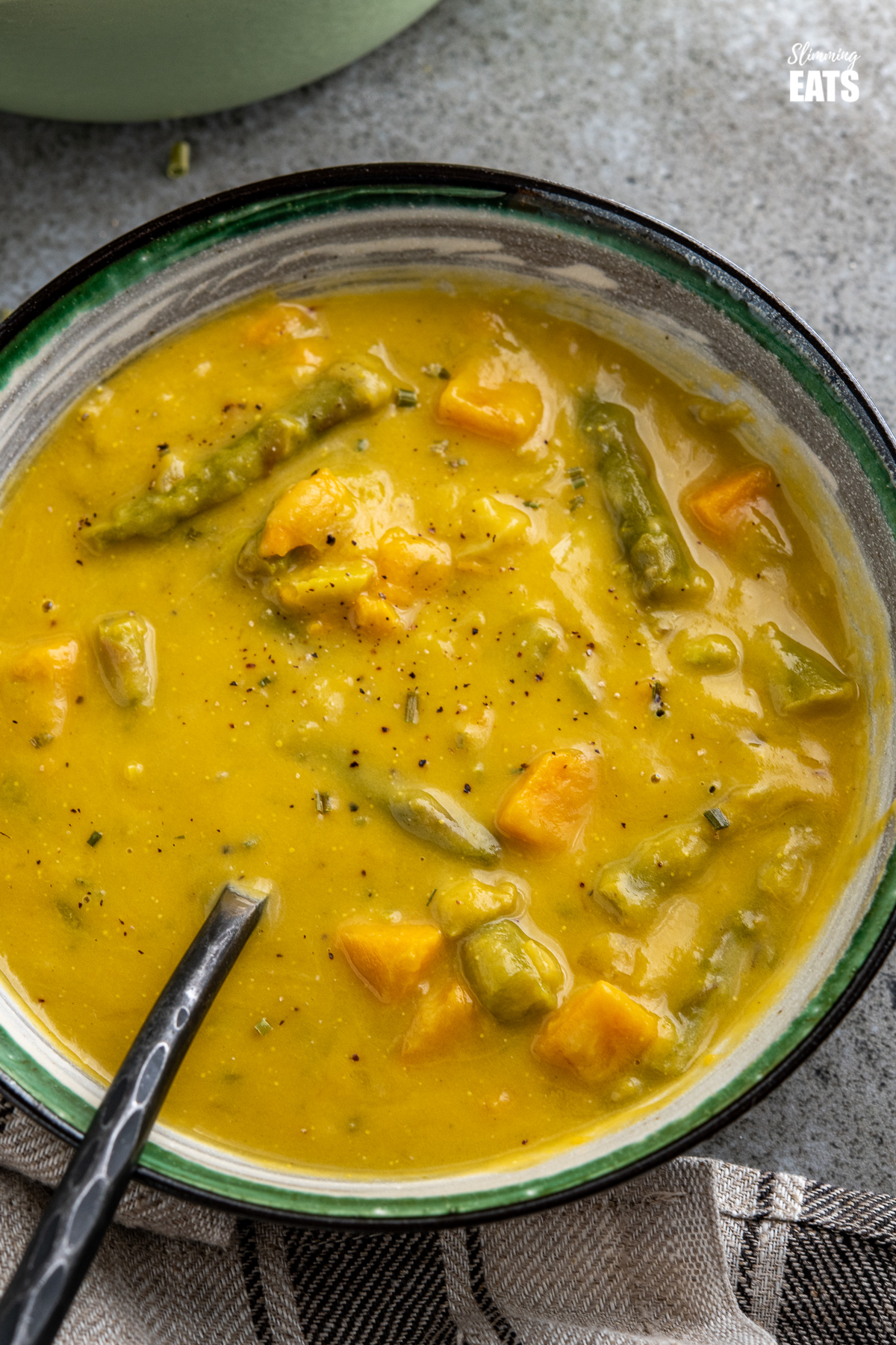 close up asparagus and sweet potato soup in white bowl with green, black and grey stripes, pan of soup in background
