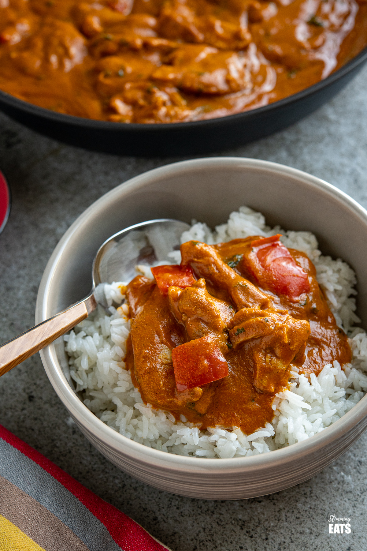 chicken curry in a grey bowl with white rice and a wooden handled spoon placed in the left hand side of the bowl