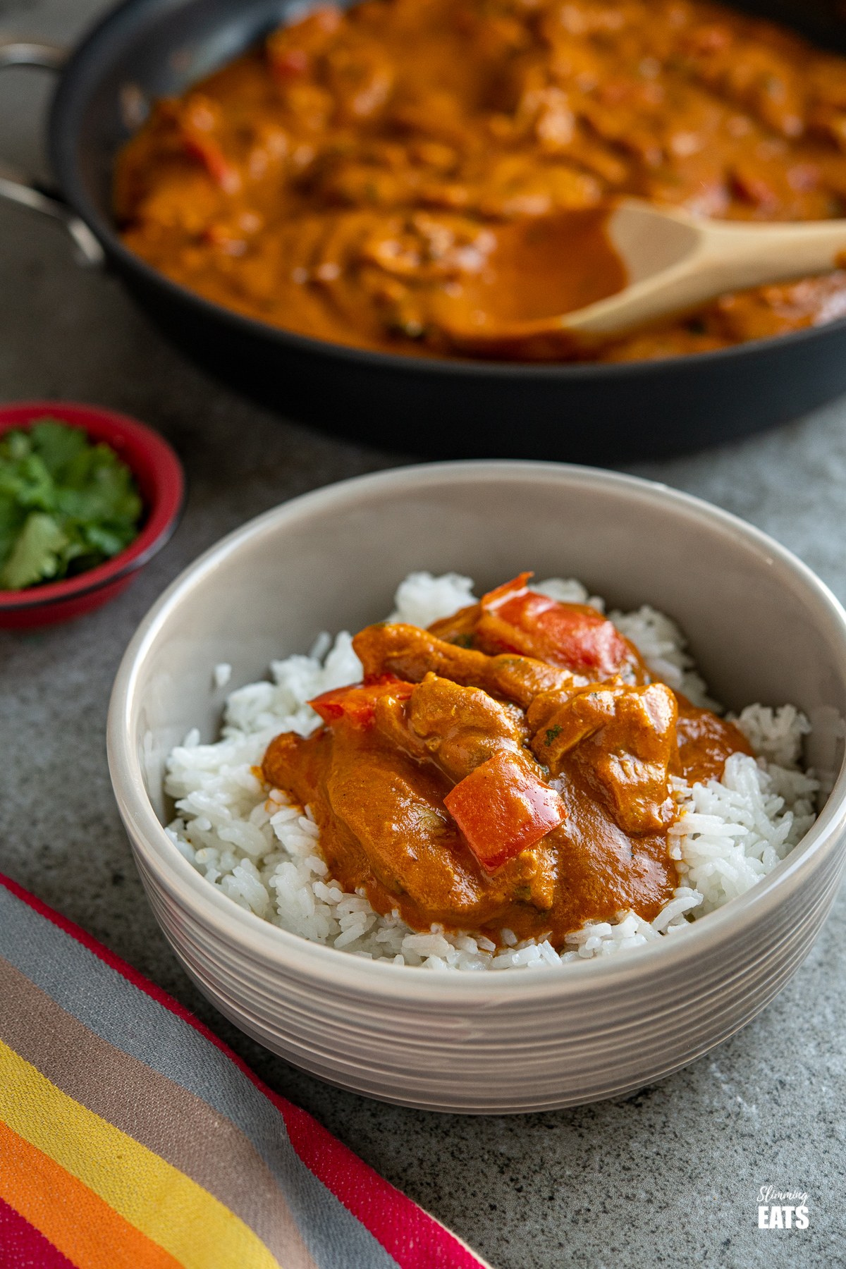 chicken curry in a grey bowl with white rice with a frying pan in the background