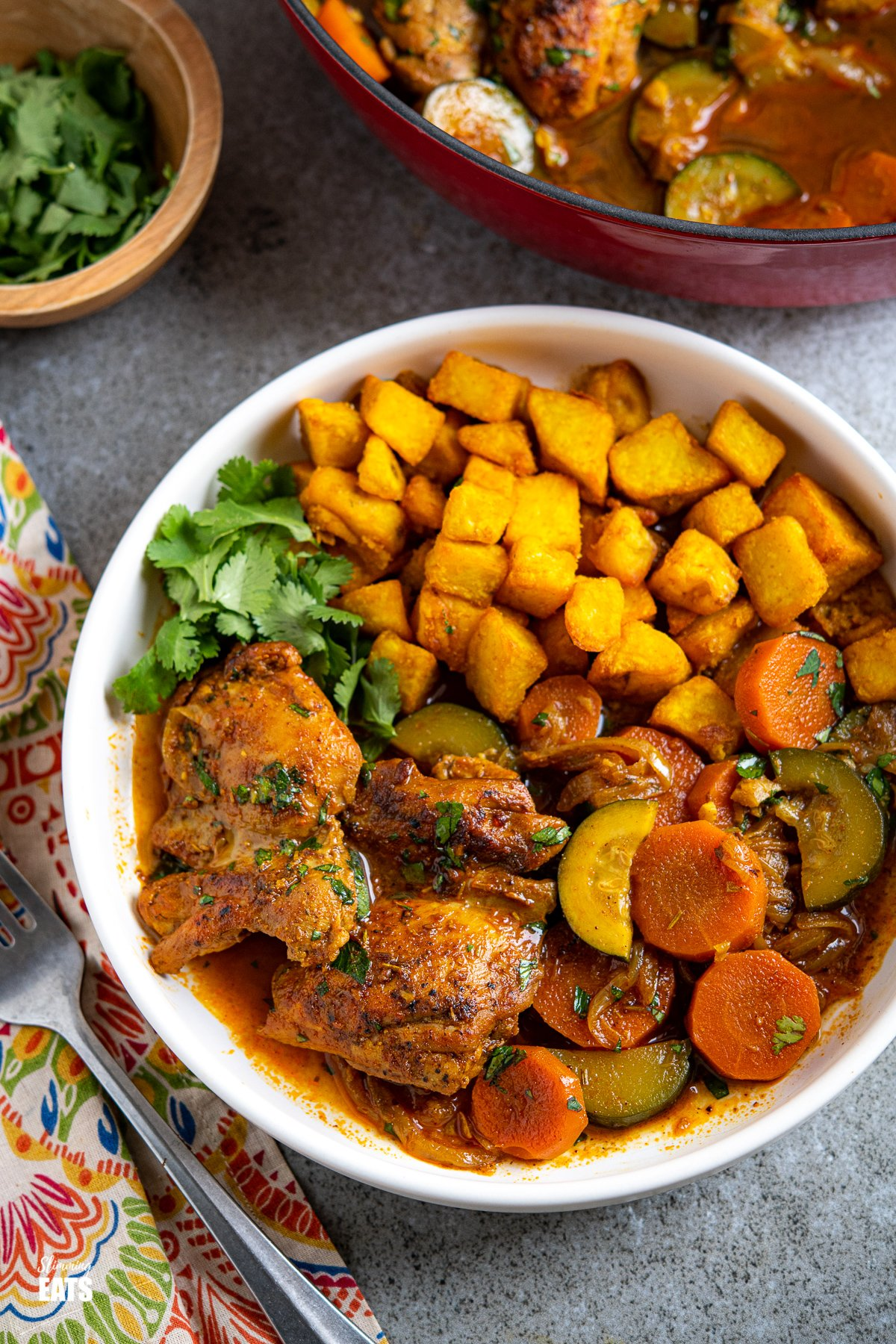 white dish with moroccan casserole and turmeric potatoes with cilantro