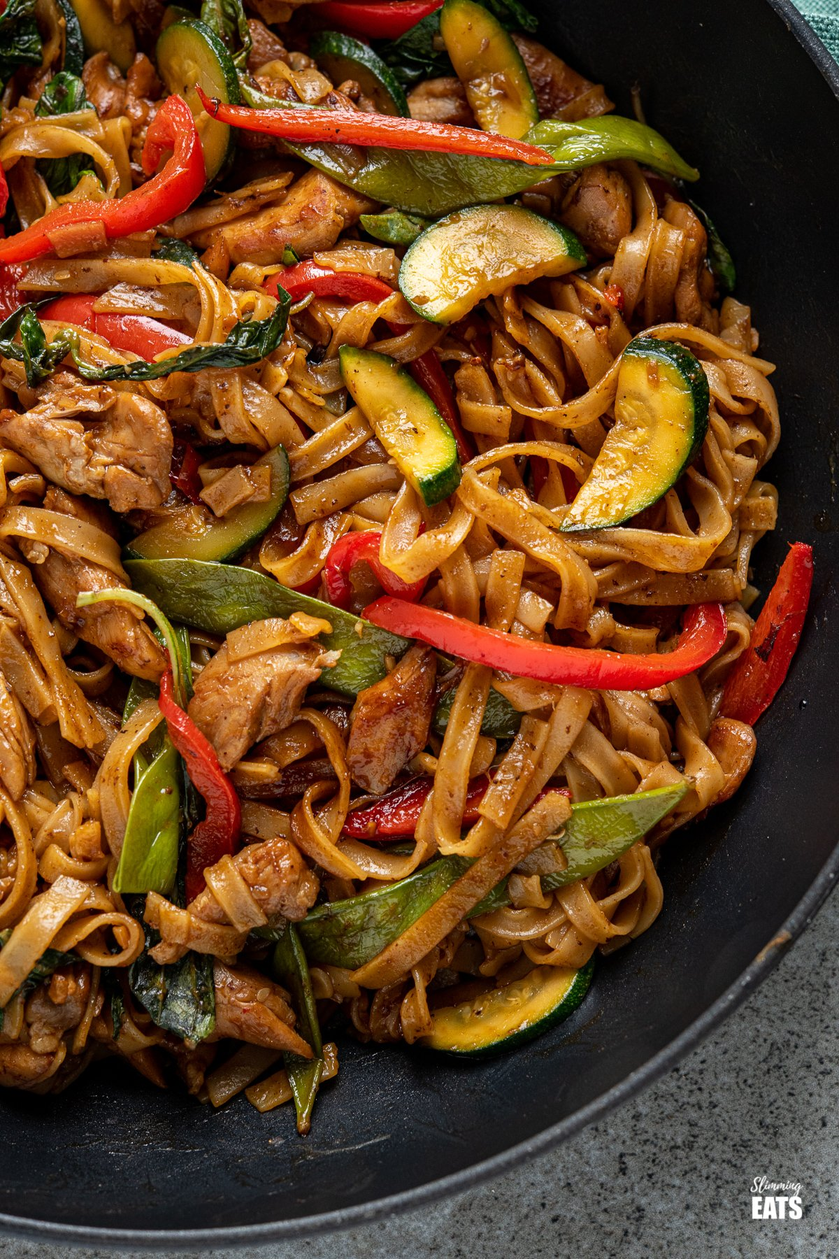 close up of drunken noodles - chicken, vegetables and rice noodles in a spicy flavoursome sauce in a black pan