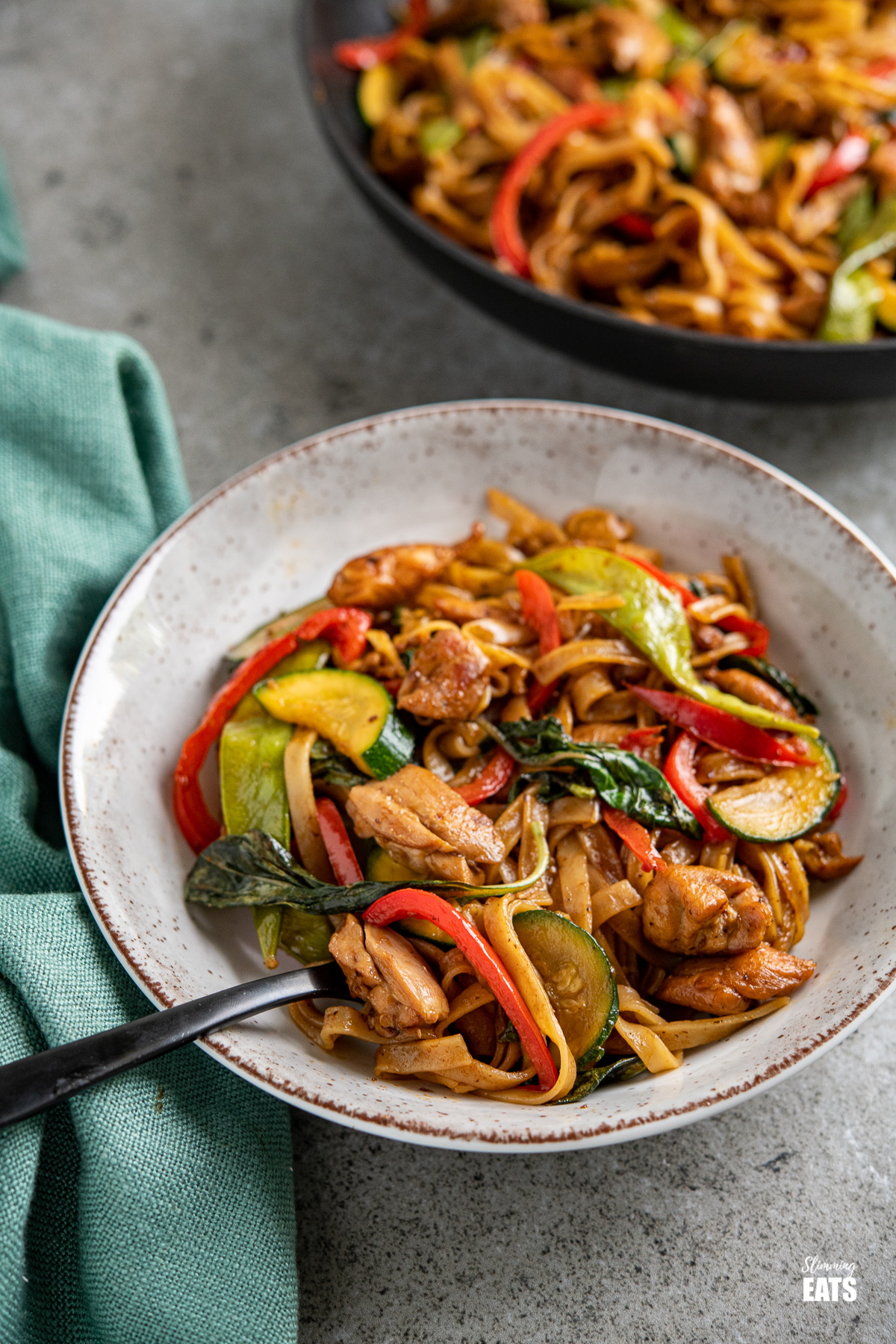 drunken noodles - chicken, vegetables and rice noodles in a spicy flavoursome sauce in a grey, brown and white bowl