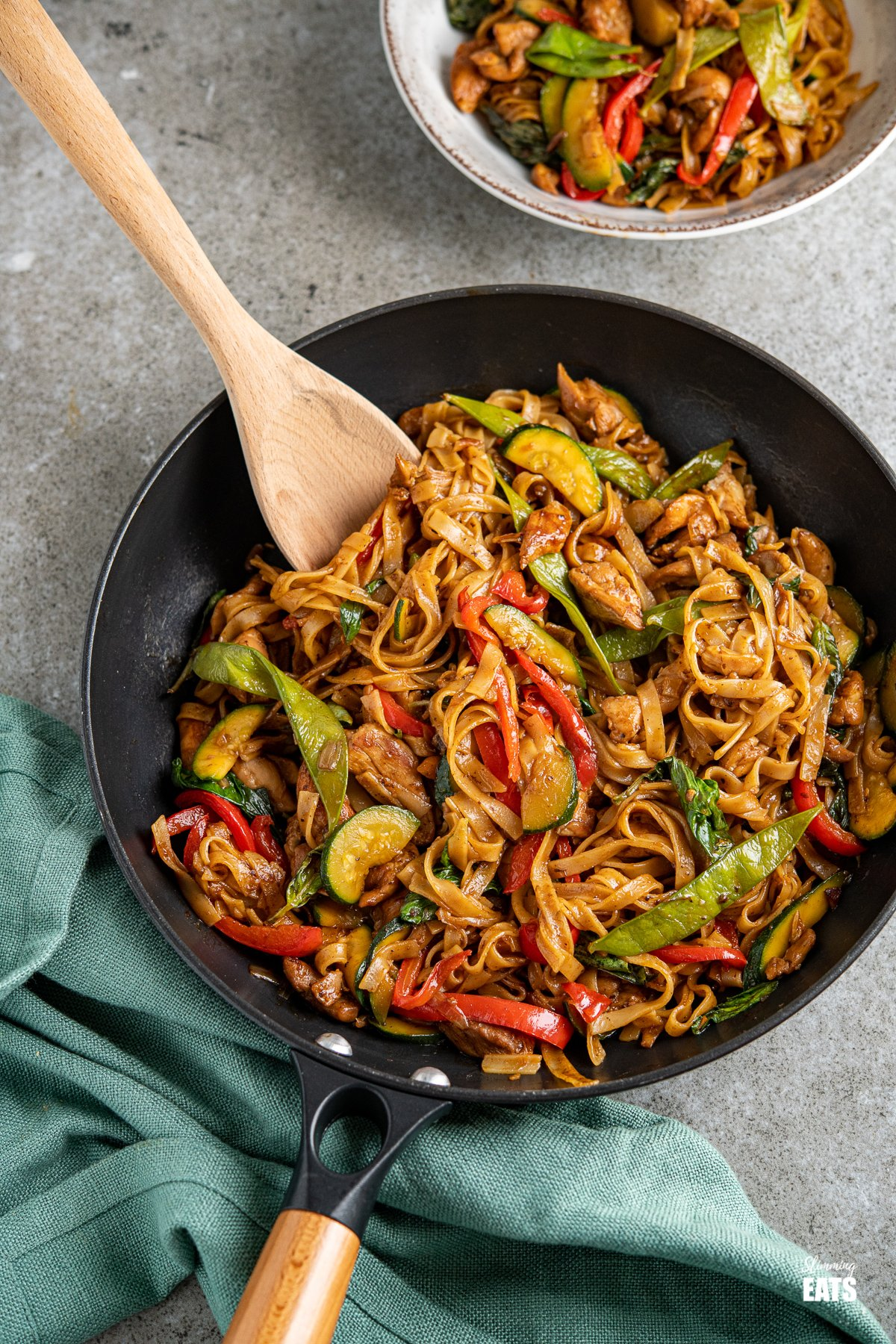 drunken noodles - chicken, vegetables and rice noodles in a spicy flavoursome sauce in a black pan with a wooden handle
