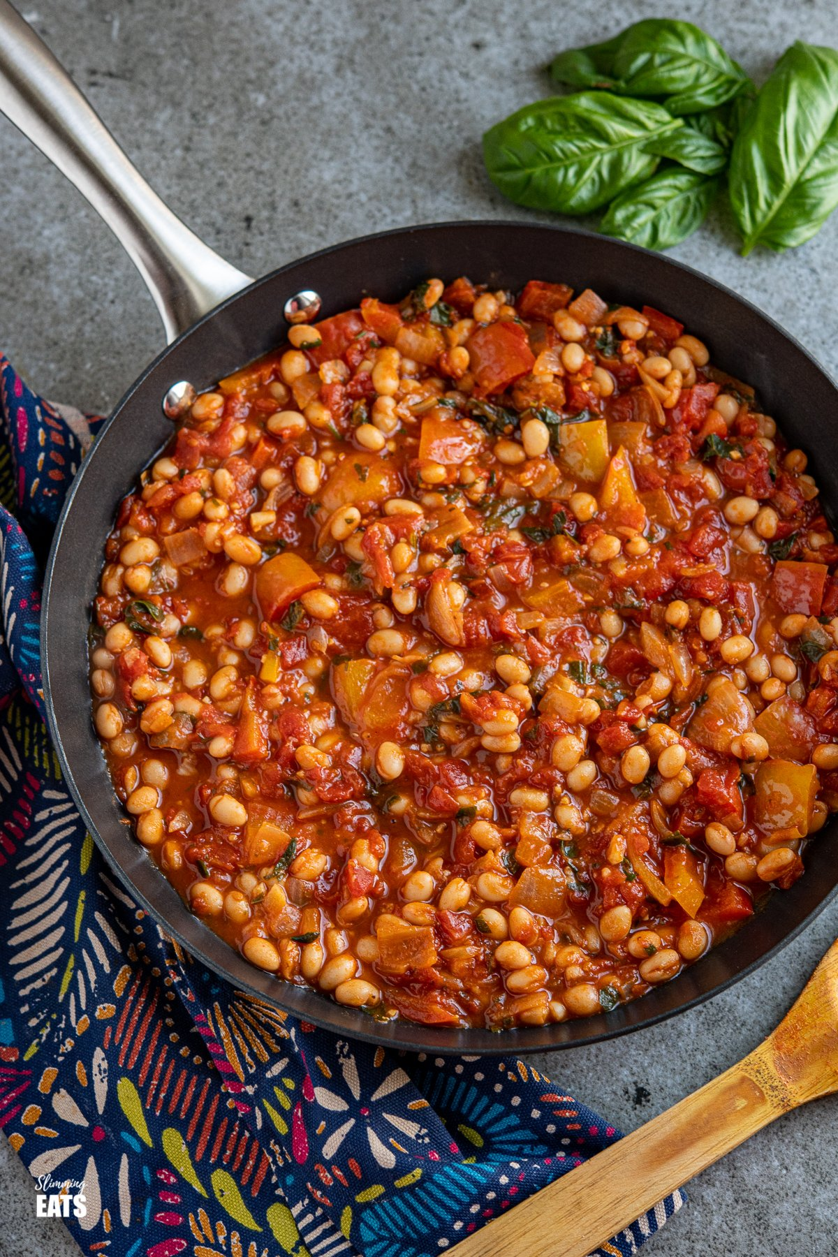 Tomatoes and White Beans in a black frying pan with a bunch of fresh basil in top right corner.