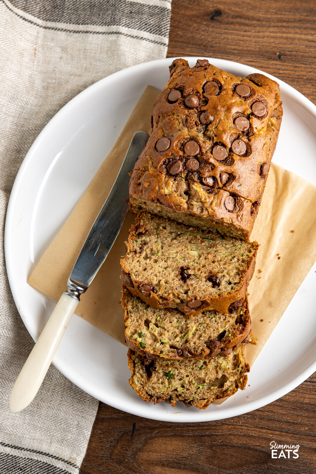 Chocolate Chip Zucchini Bread on white plate sliced with knife to thje left