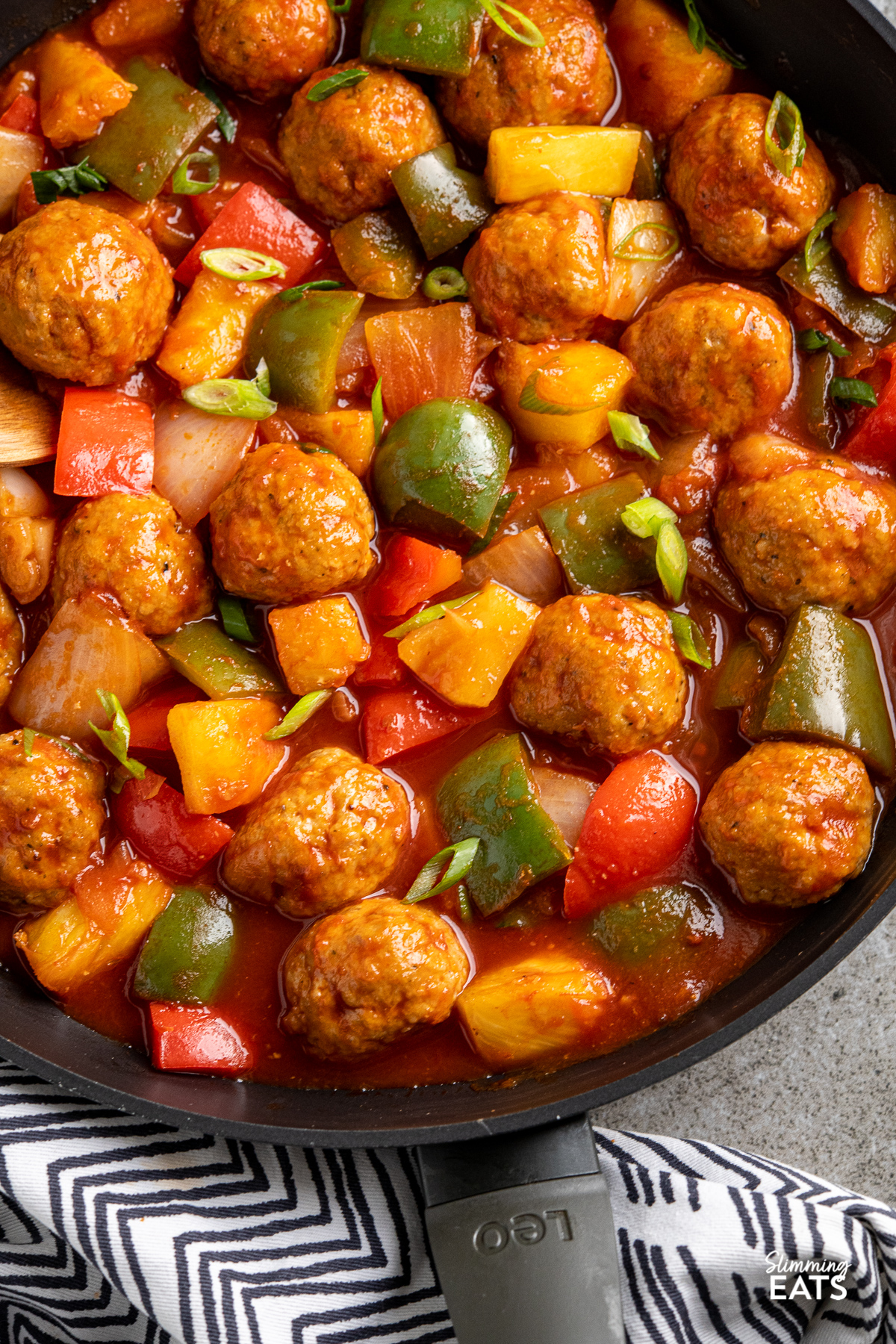 close up of sweet and sour chicken meatballs in black frying pan with vegetables and pineapple