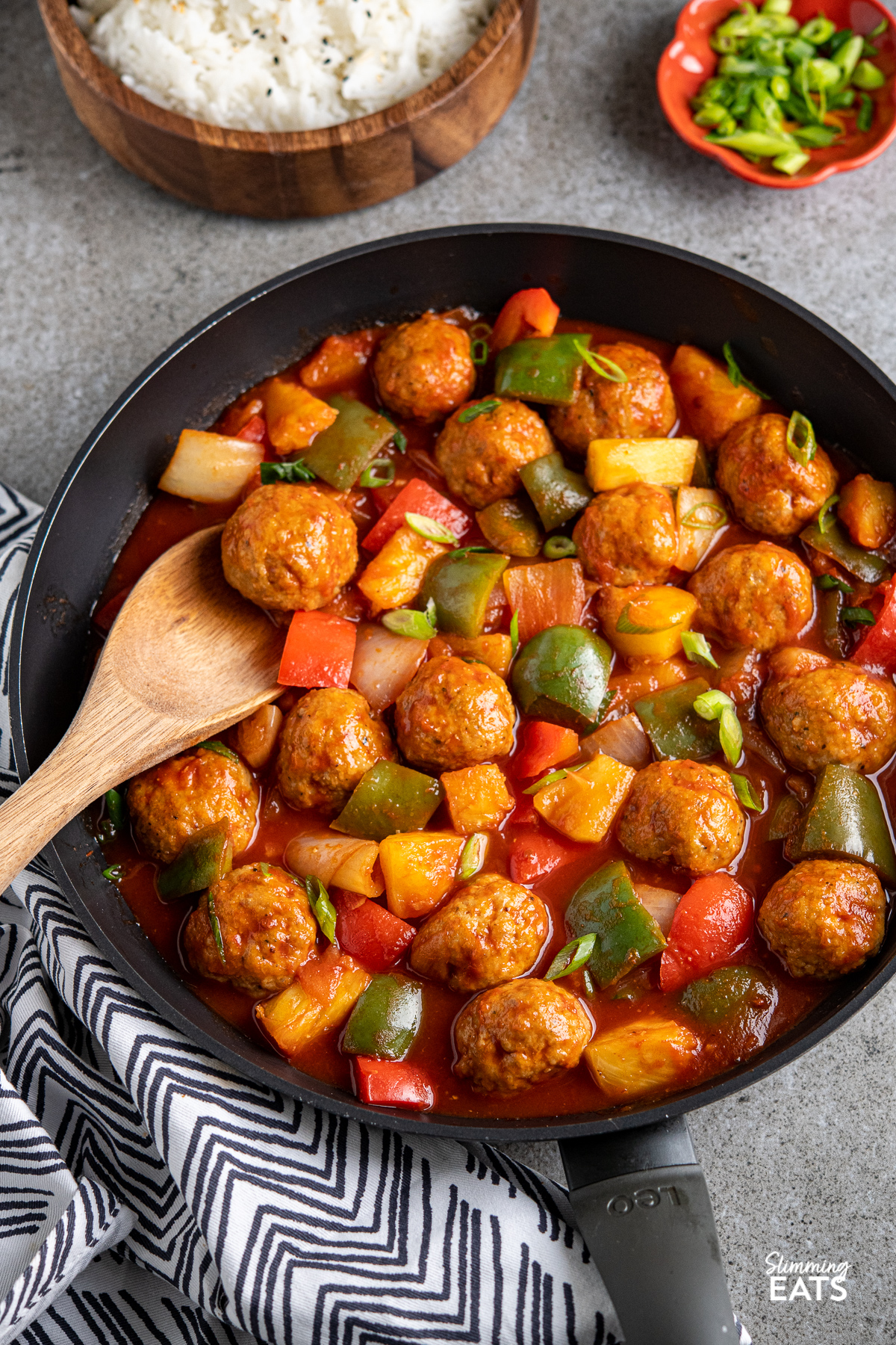 sweet and sour chicken meatballs in a black frying pan with vegetables, wooden bowl of jasmine rice in background and terracotta pinch bowl with spring onions