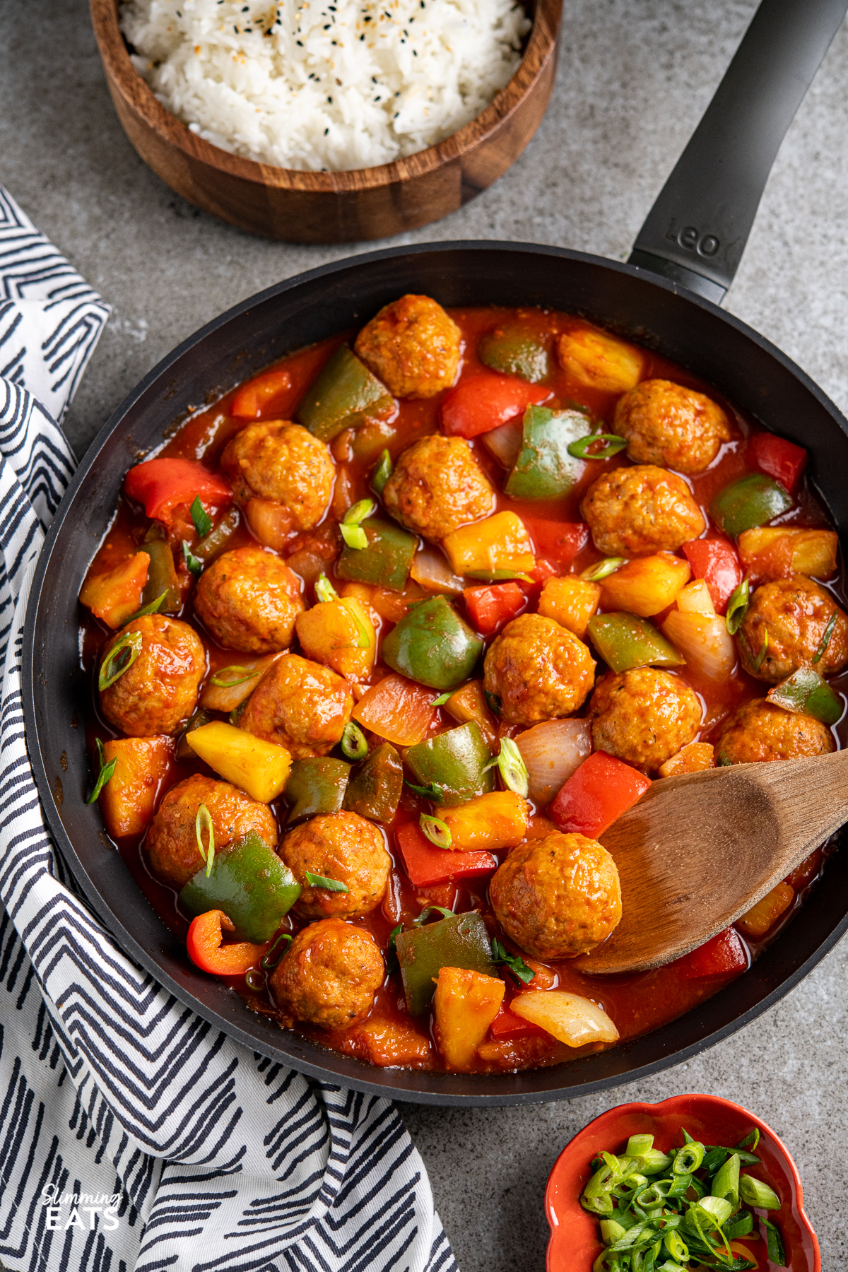 sweet and sour chicken meatballs in a black frying pan with vegetables and a wooden bowl of jasmine rice in background