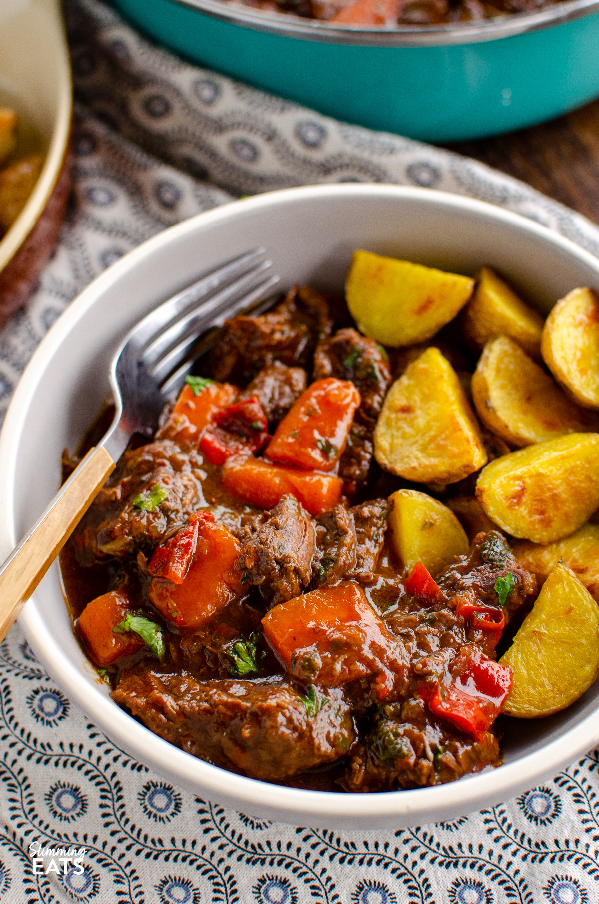 grey bowl of balsamic braised beef with roasted Yukon gold potatoes on a patterned placemat
