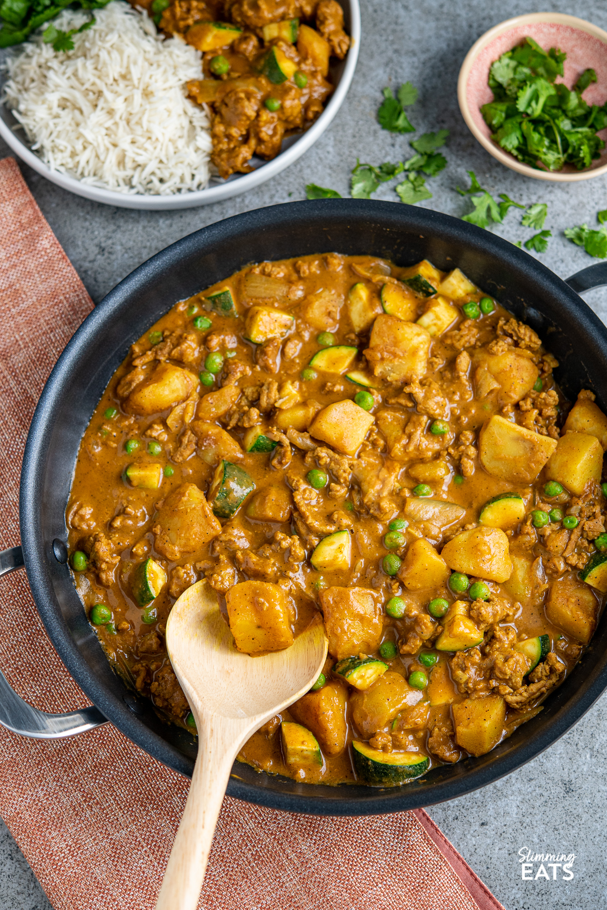 ground turkey and potato curry in black double handled frying pan with serving on a plate in backround wiht rice and small bowl of fresh coriander