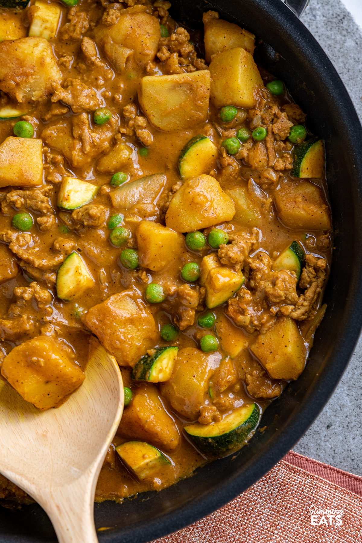close up of ground turkey and potato curry in black frying pan
