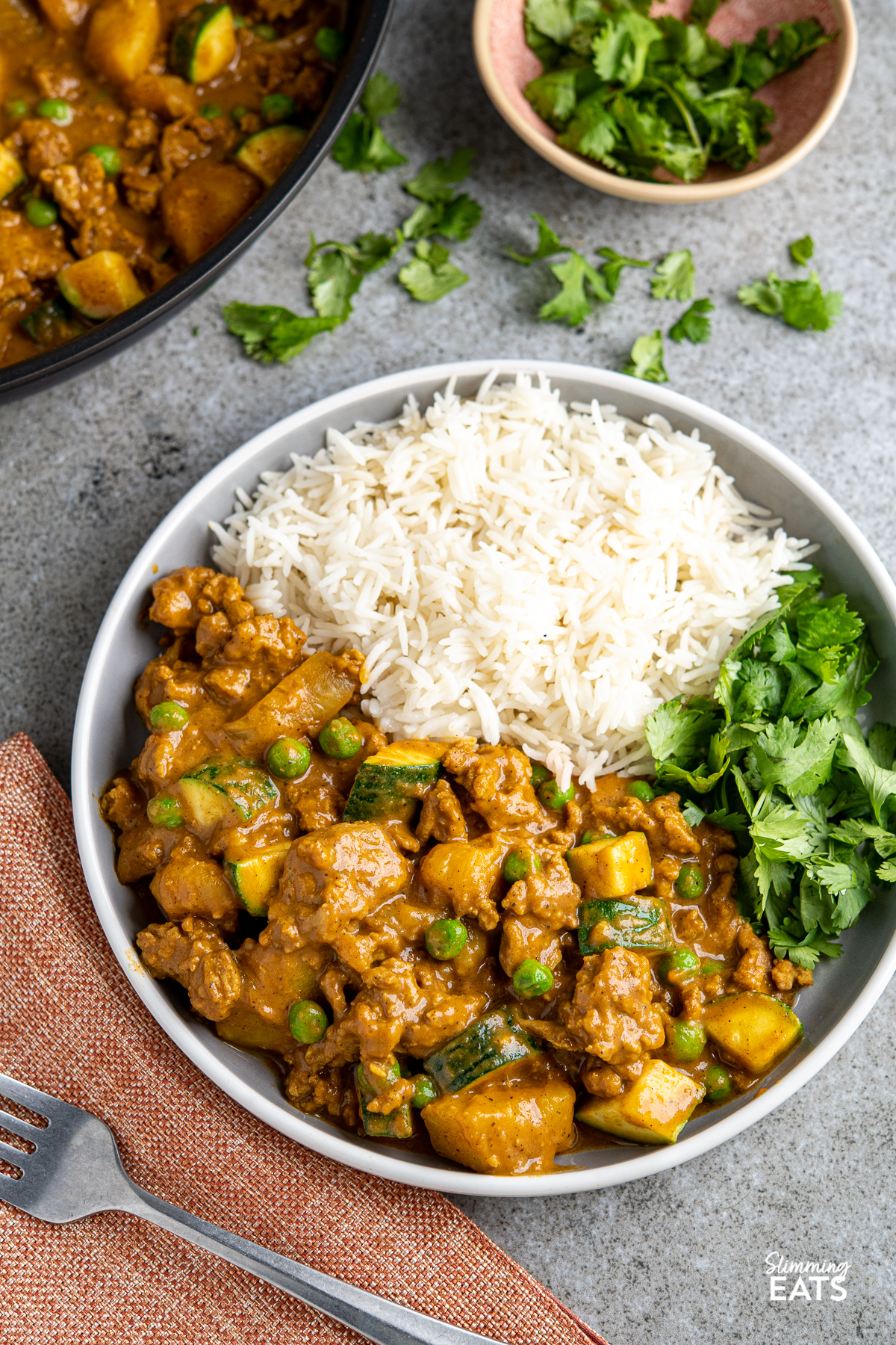 Ground Turkey Potato Curry served up on grey plate with white rim with rice and fresh coriander