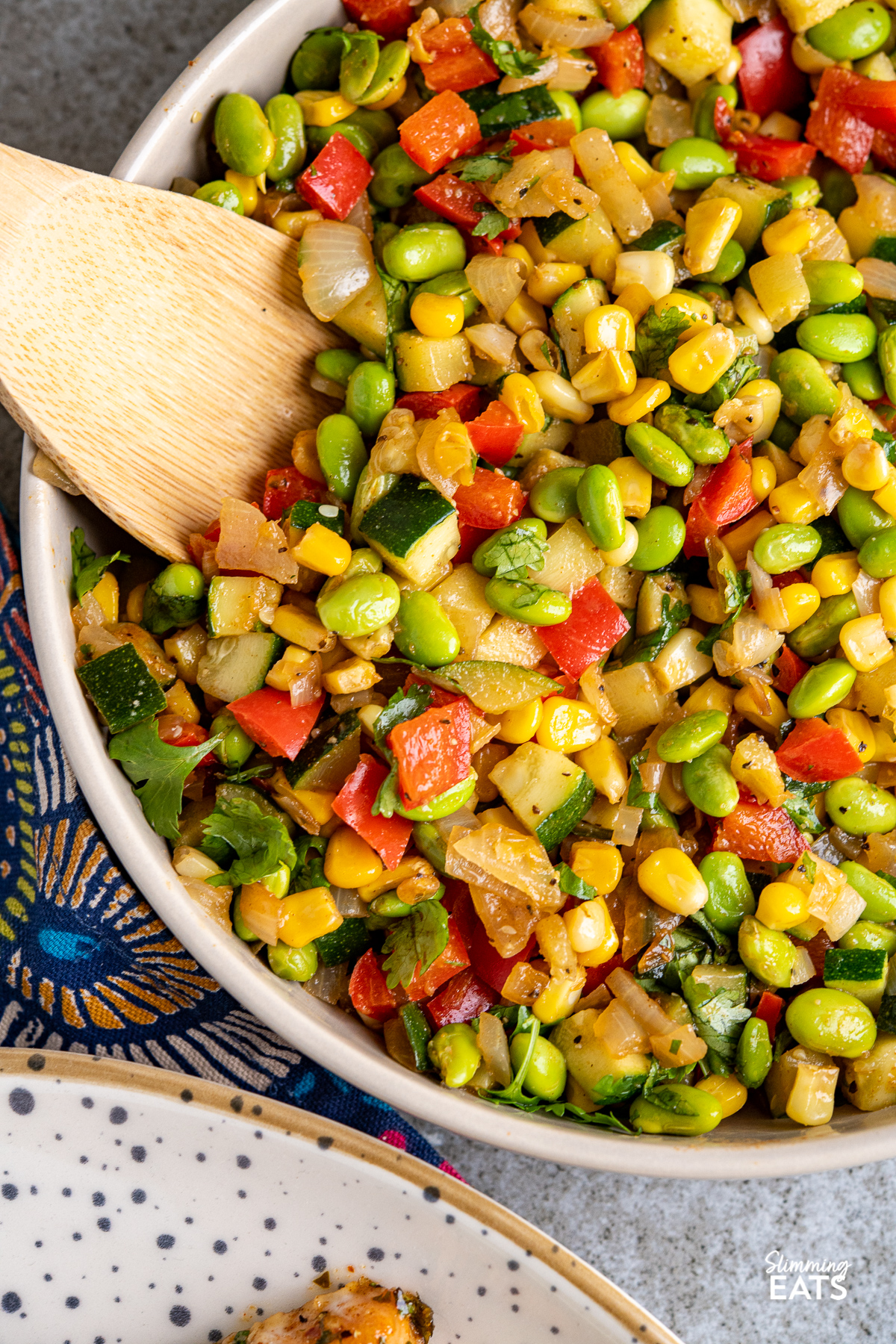 close up of beige bowl with sauteed vegetables, corn and edamame