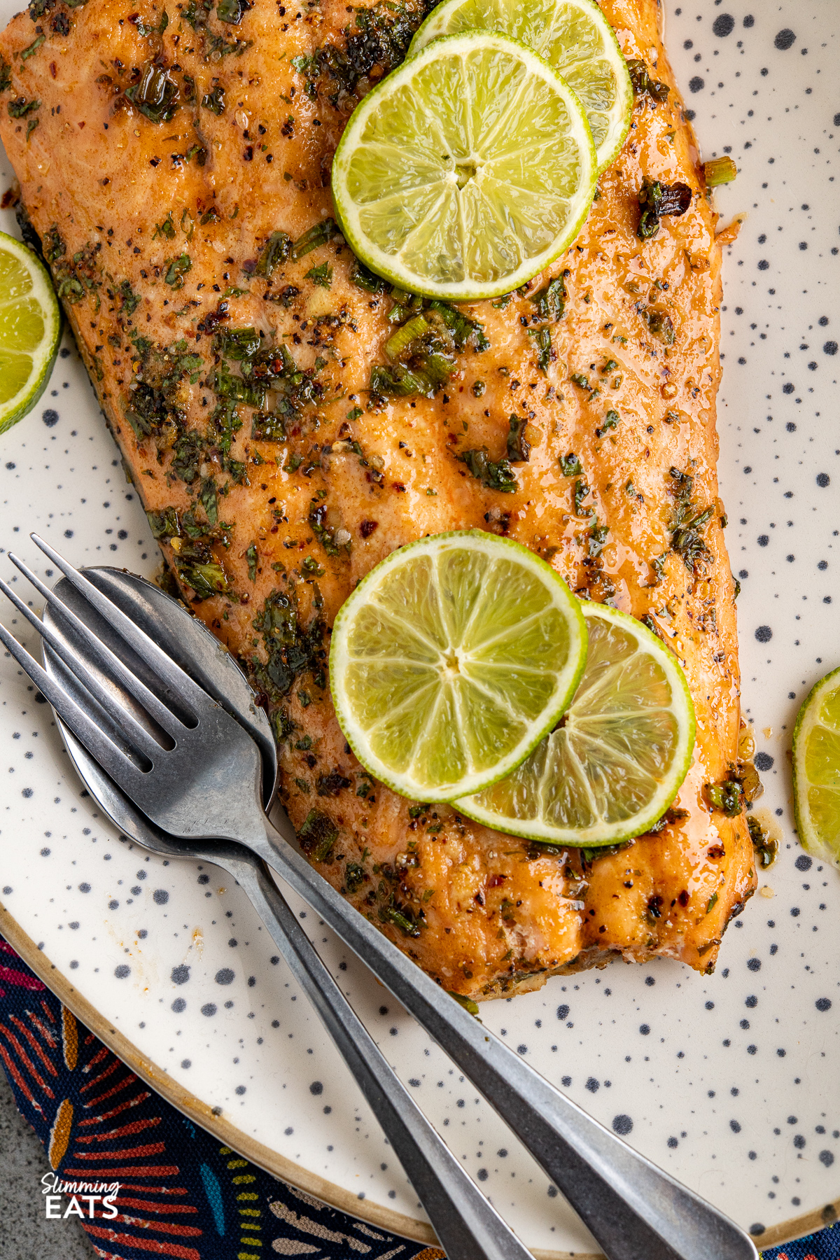 close up of honey lime and chilli salmon fillet with lime slices on a large speckled oval plate