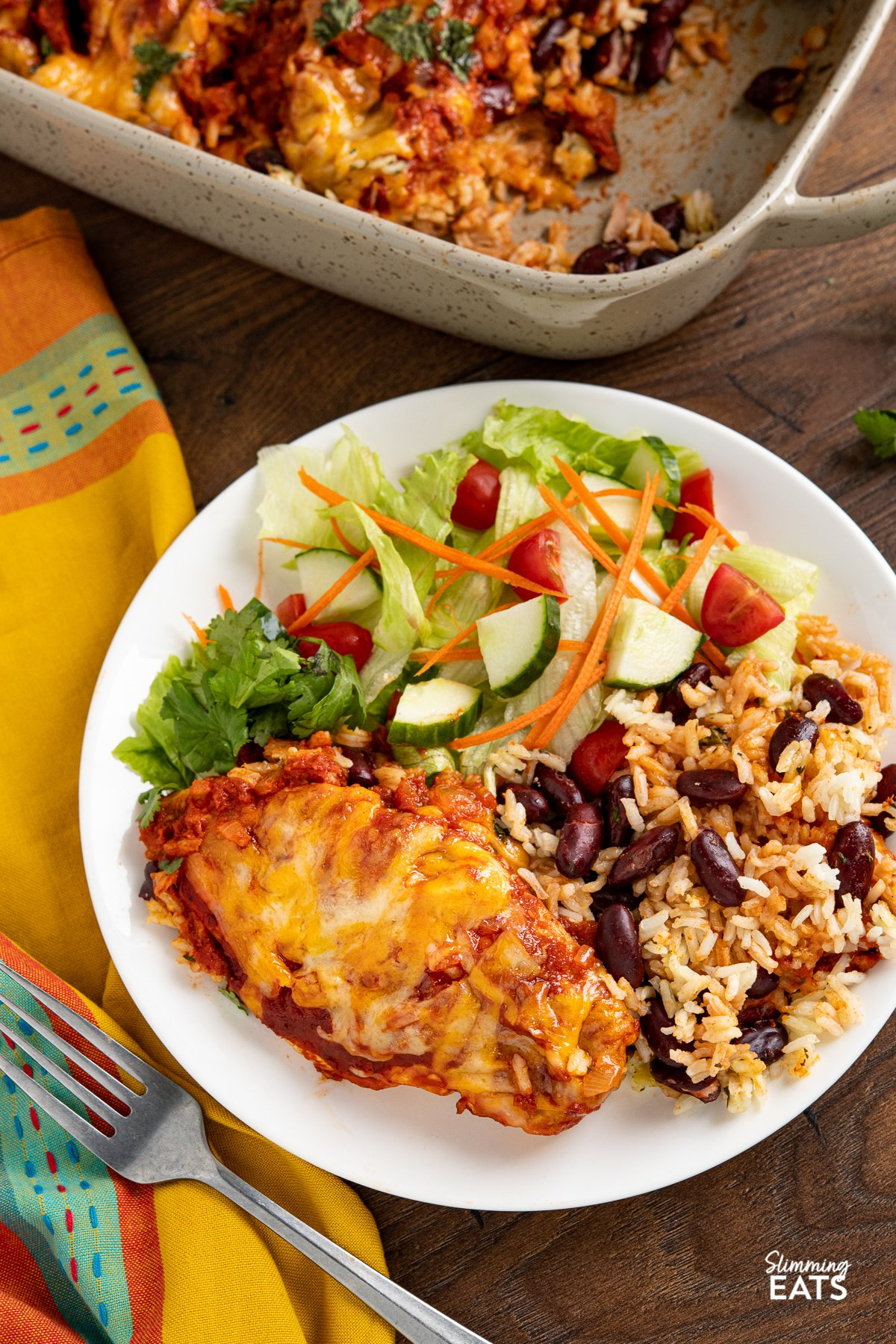 serving of Mexican Chicken and Rice Bake on a white plate with a mixed salad of lettuce, tomatoes, cucumber and carrot.