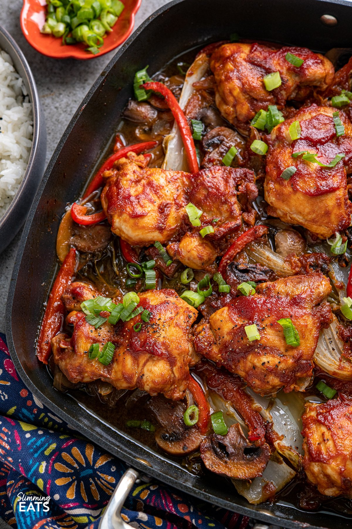 close up of Sriracha Peach Chicken Bake with vegetables in square All-Clad skillet  with dark grey bowl of rice and pinch bowl with sliced spring onions