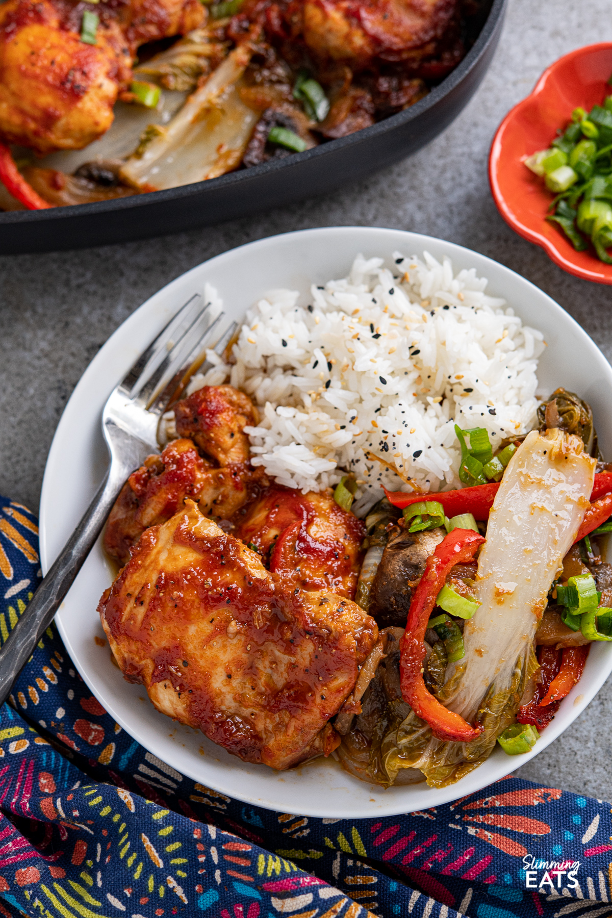 white bowl with Sriracha Peach Chicken Bake and jasmine rice with mixed sesame seeds and vegetables, skillet and pinch bowl visible in back ground.