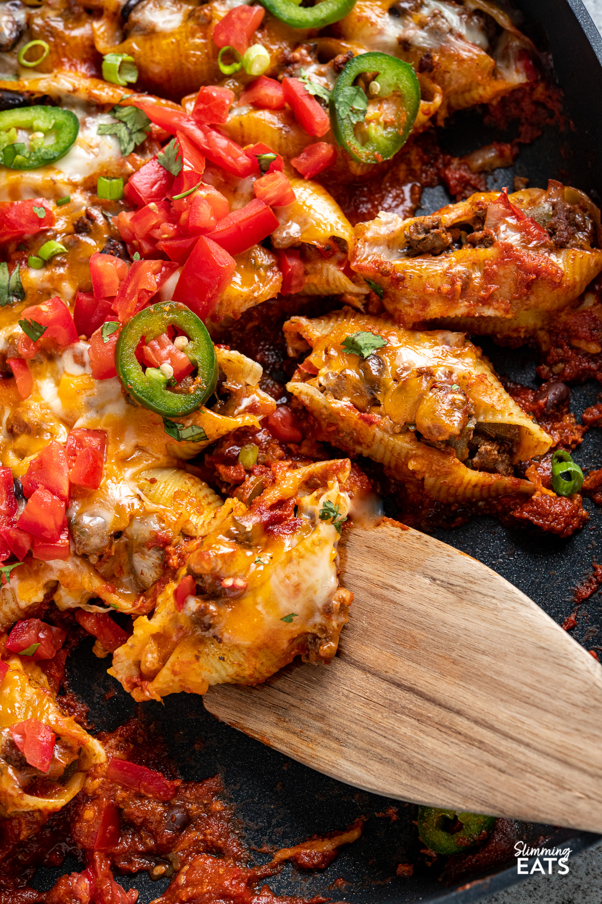 close up  of Cheesy Beef Enchilada Stuffed Pasta Shells in all-clad skillet