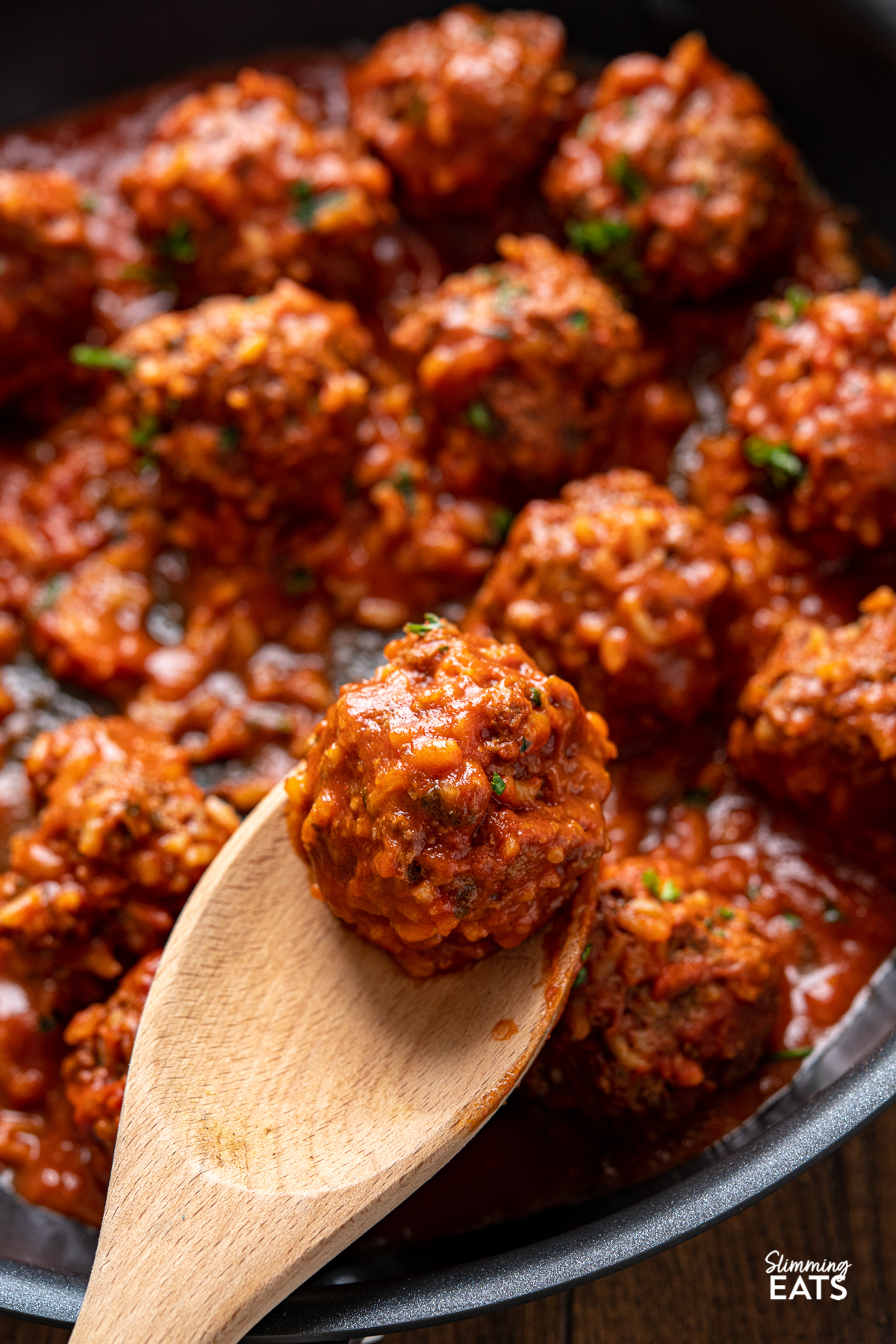 close up of Porcupine Meatballs on wooden spoon in black skillet